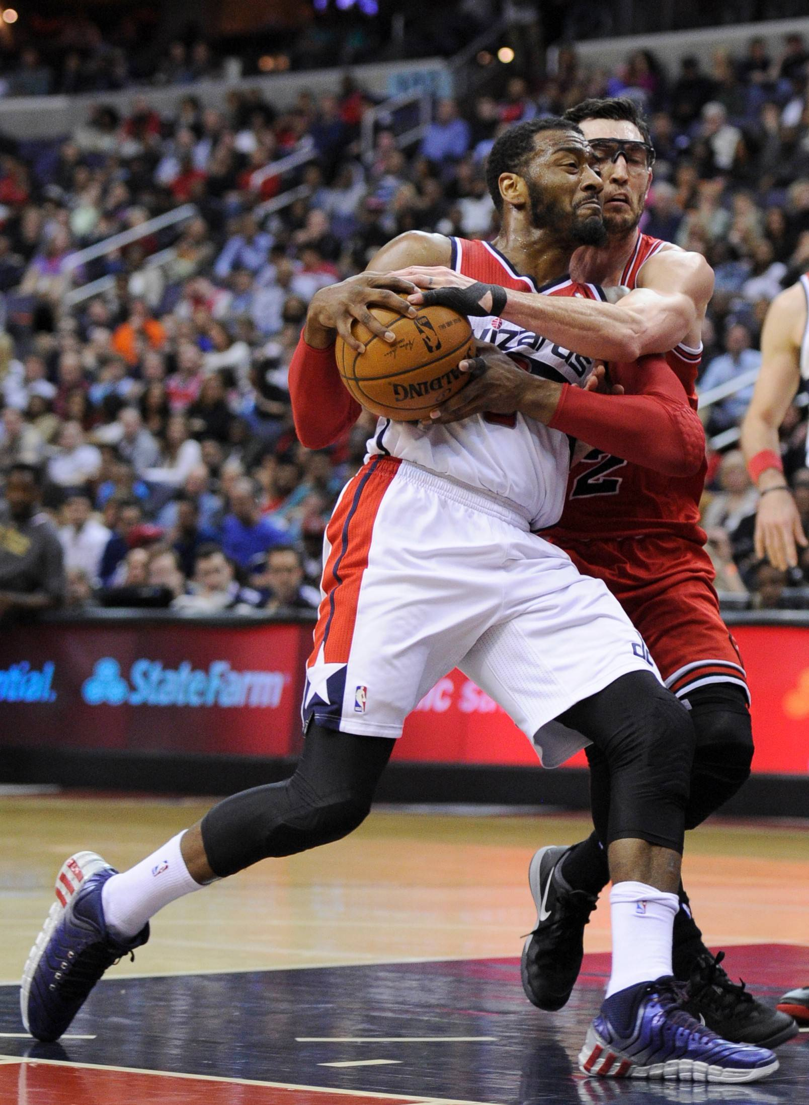 Chicago Bulls guard Kirk Hinrich, right, grabs Washington Wizards guard John Wall during the second half of an NBA basketball game, Saturday, April 5, 2014, in Washington. Hinrich was called for a foul on the play. The Bulls won 96-78.