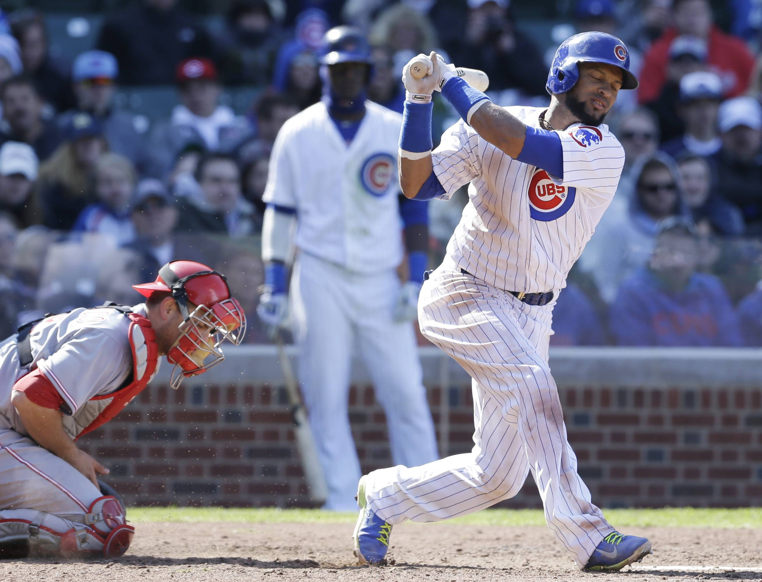 Chicago Cubs' Emilio Bonifacio, right, strikes out swinging during the seventh inning of a baseball game against the Cincinnati Reds in Chicago, Friday, April  18, 2014. The Reds won 4-1.