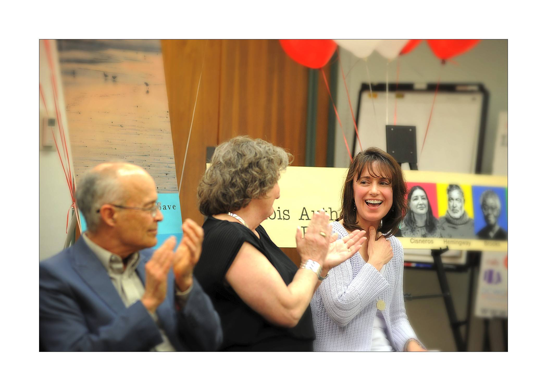 Joanne Zienty, right, of Wheaton reacts to being the winner of the Soon to be Famous Illinois Author award at a reception Wednesday at the Reaching Across Illinois Library System offices in Burr Ridge. Seated next to her are the other two finalists, Rick Polad of Carol Stream and Mary Hutchings Reed of Chicago.