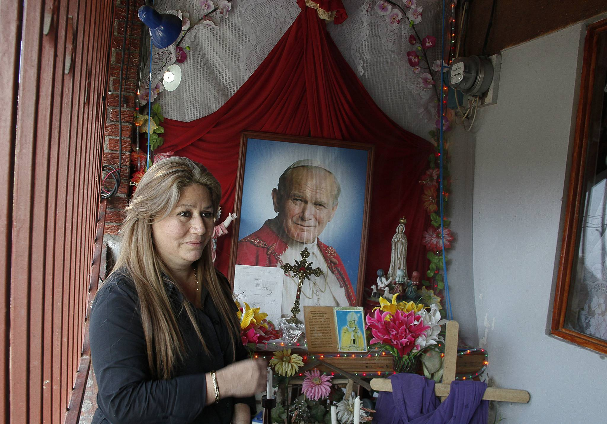 Floribeth Mora stands by her shrine to Pope John Paul II inside the entrance to her home in La Union de Cartago, Costa Rica. Mora, her doctors and the Catholic Church say her aneurysm disappeared in May of 2011 in a miracle that cleared the way for the late pope to be declared a saint.