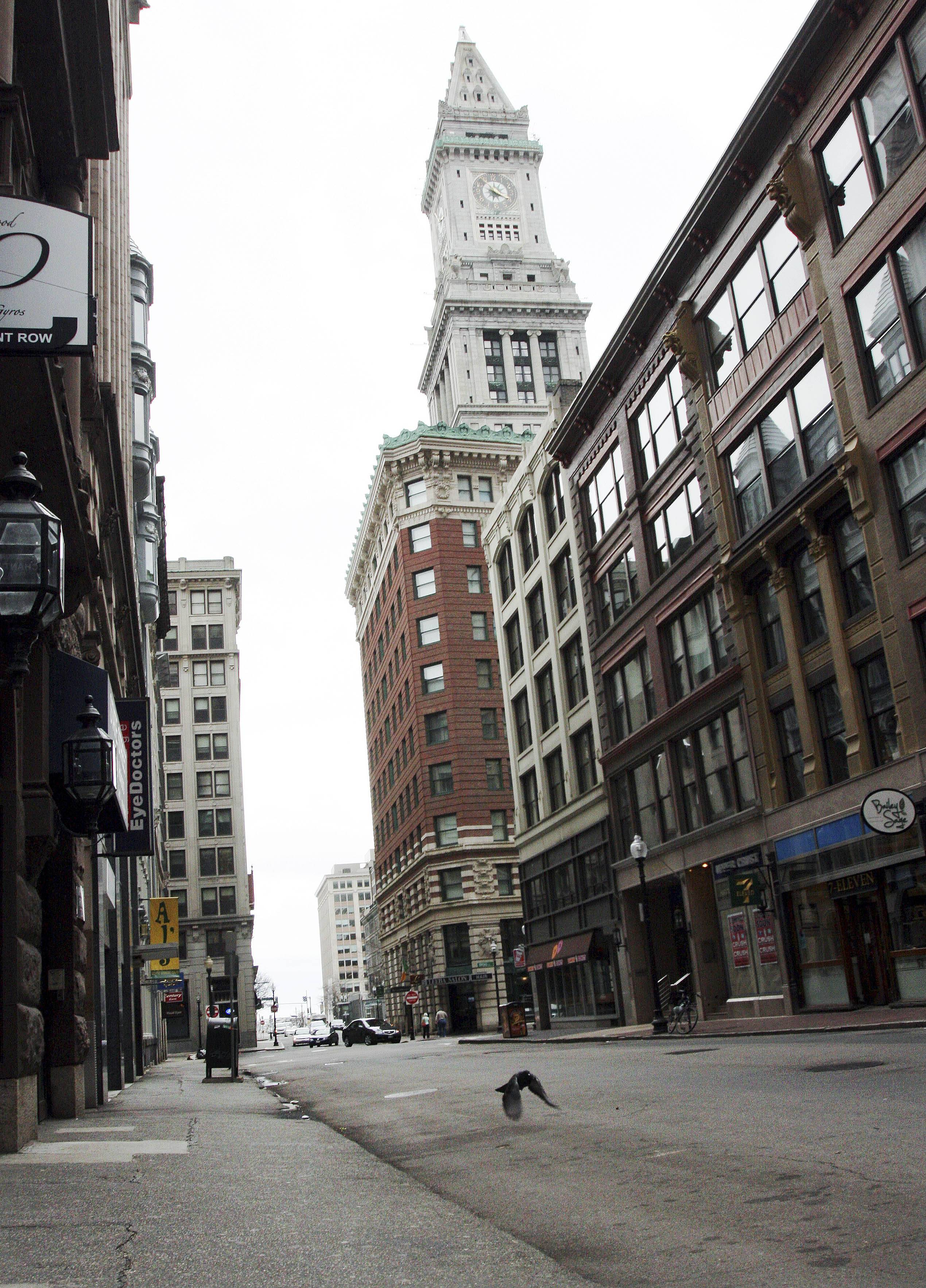 A pigeon flies along deserted State Street with the Custom House hotel in the background in downtown Boston. Mass transit was suspended while a suspect was hunted following bombings near the finish line of the Boston Marathon.