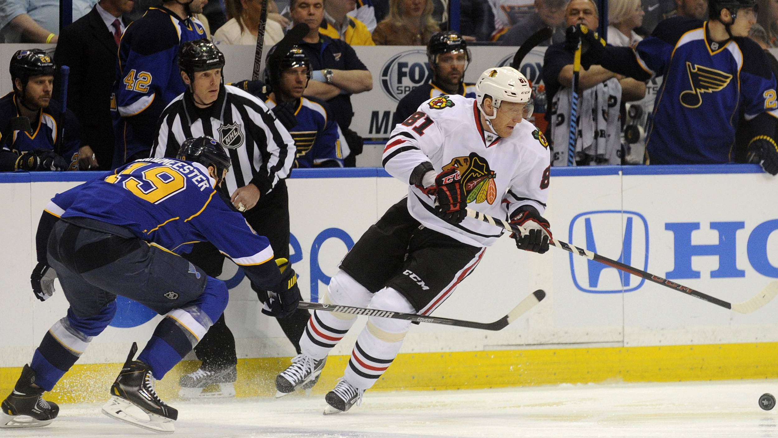 Chicago Blackhawks' Marian Hossa (81), of Sweden, and St. Louis Blues' Jay Bouwmeester (19) reach for a loose puck during the first period in Game 2 of a first-round NHL hockey playoff series on Saturday, April 19, 2014, in St. Louis.