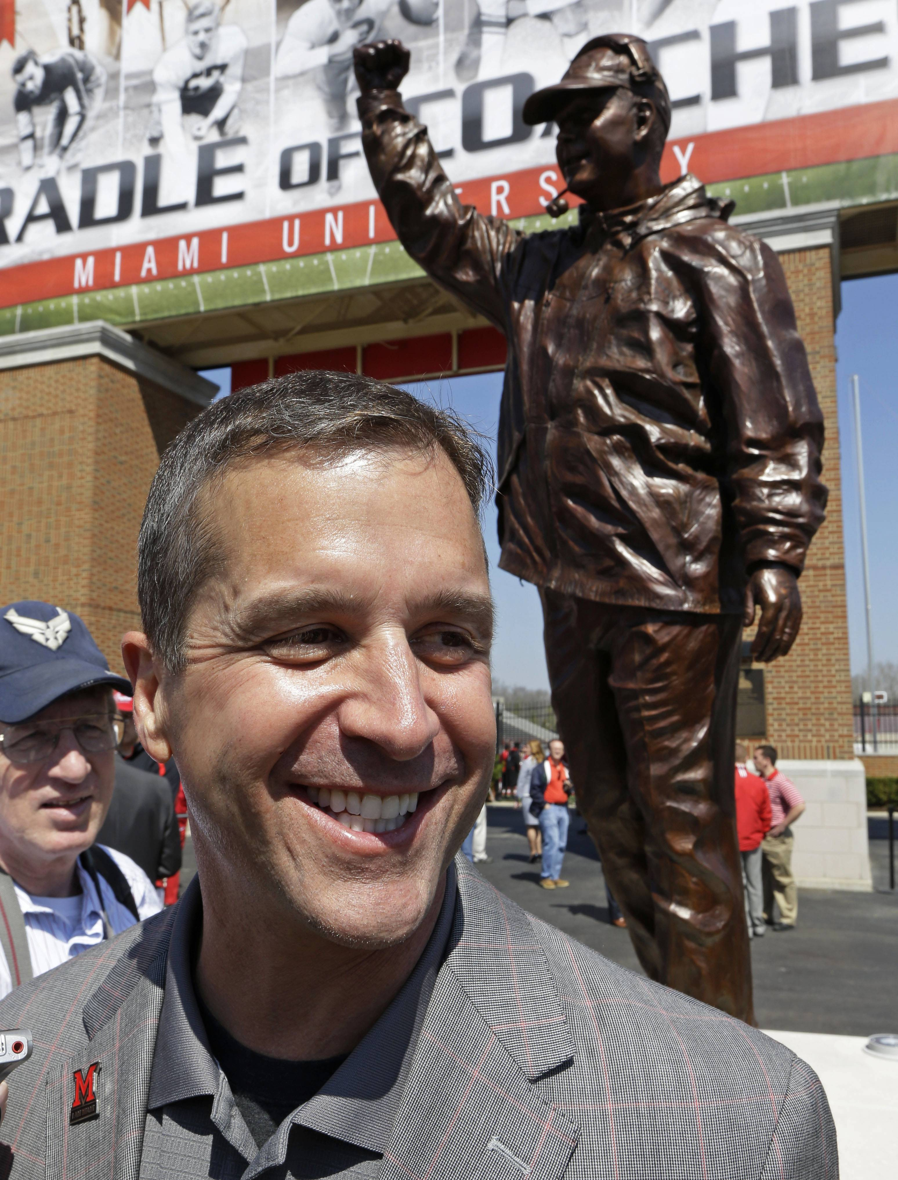 Baltimore Ravens coach John Harbaugh smiles next to a statue of him that was unveiled Saturday at Miami (Ohio) University in Oxford, Ohio, where Harbaugh was inducted into the school's Cradle of Coaches.
