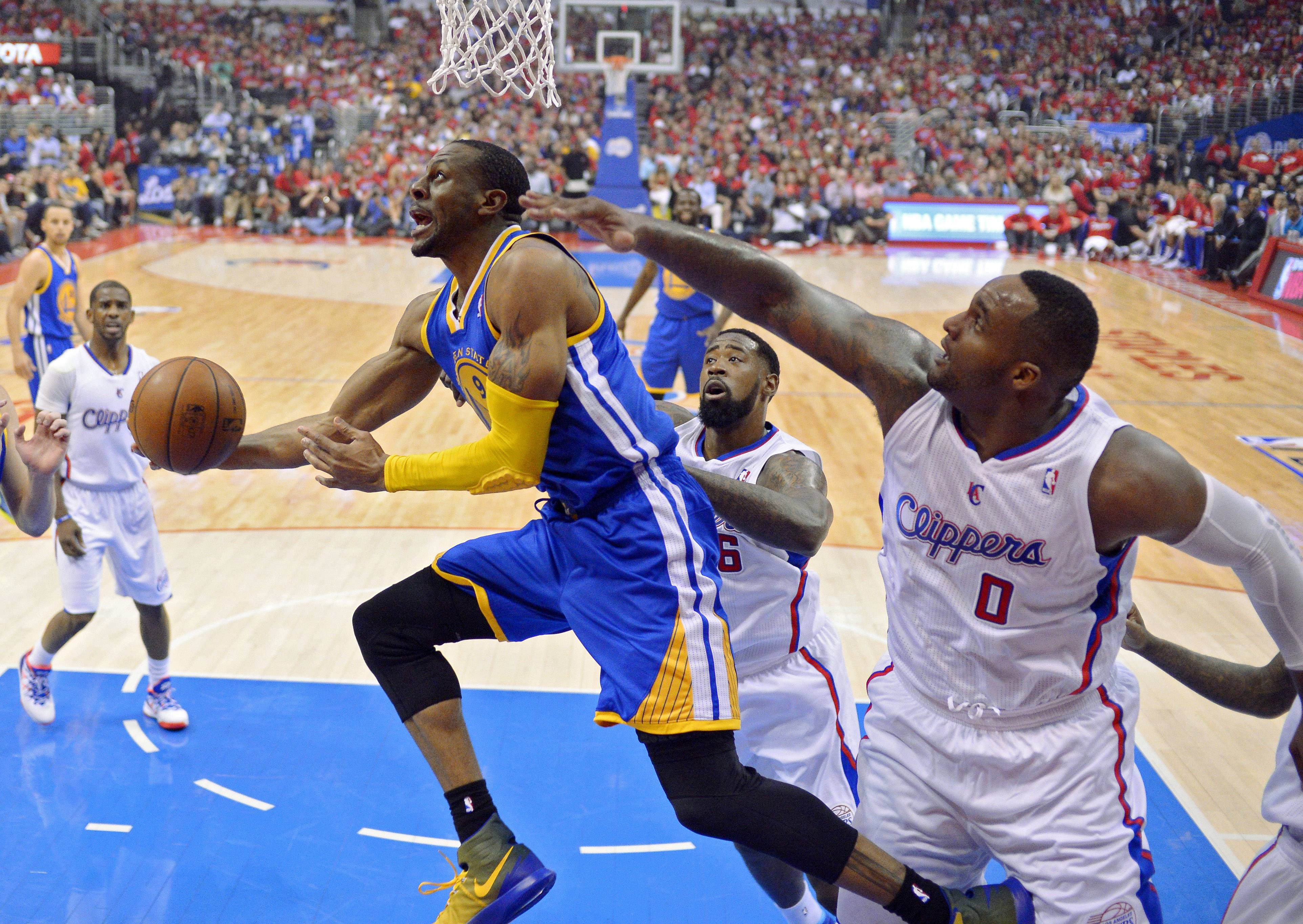 Golden State Warriors forward Andre Iguodala, left, puts up a shot as Los Angeles Clippers center DeAndre Jordan, center, and forward Glen Davis defend during Game 1 of an opening-round NBA basketball playoff series Saturday in Los Angeles.