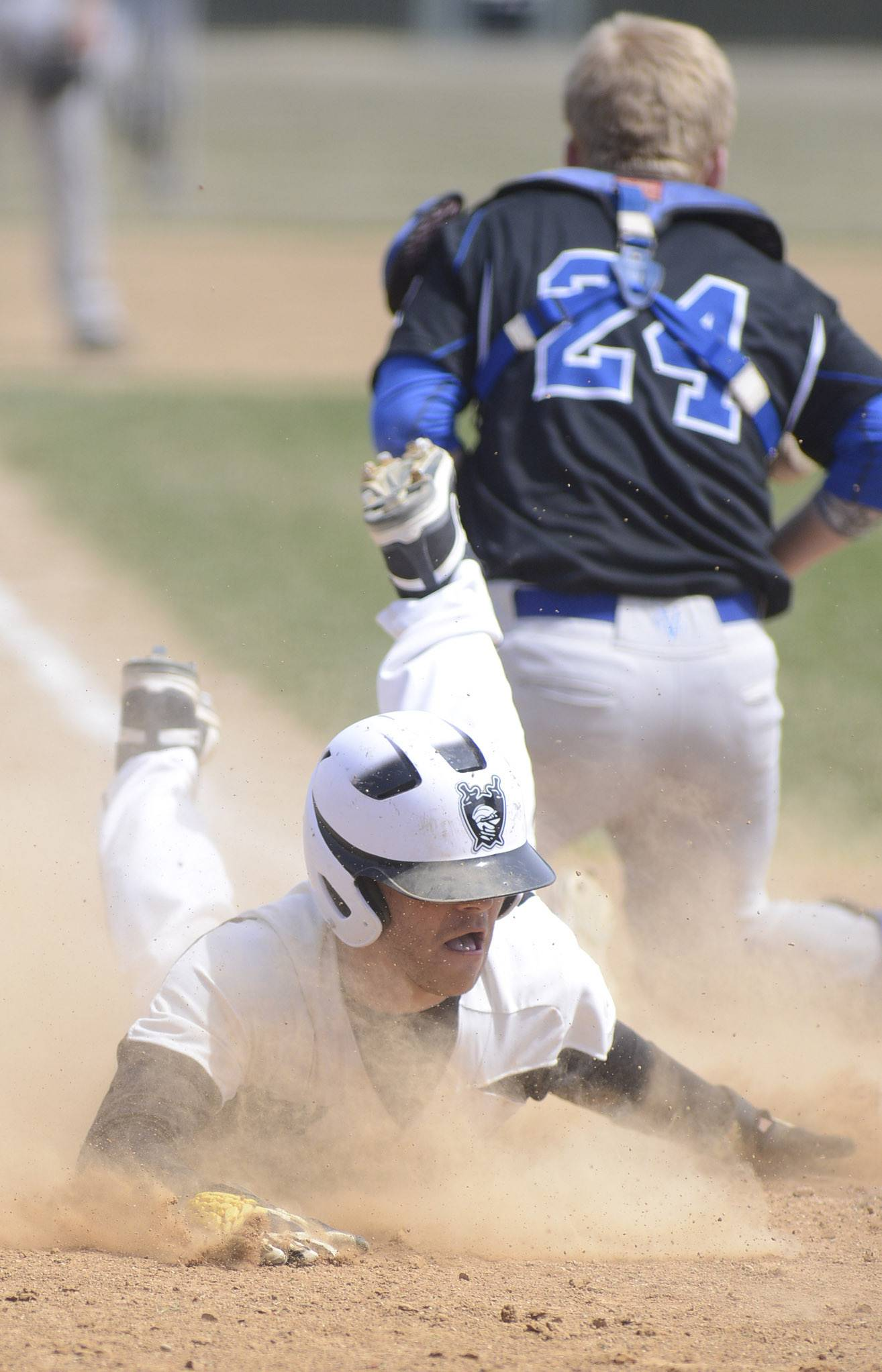 Kaneland's Joe Panico slides into home plate past Geneva catcher Nathan Montgomery to break a 6-6 tie in the ninth inning on Saturday in Maple Park.