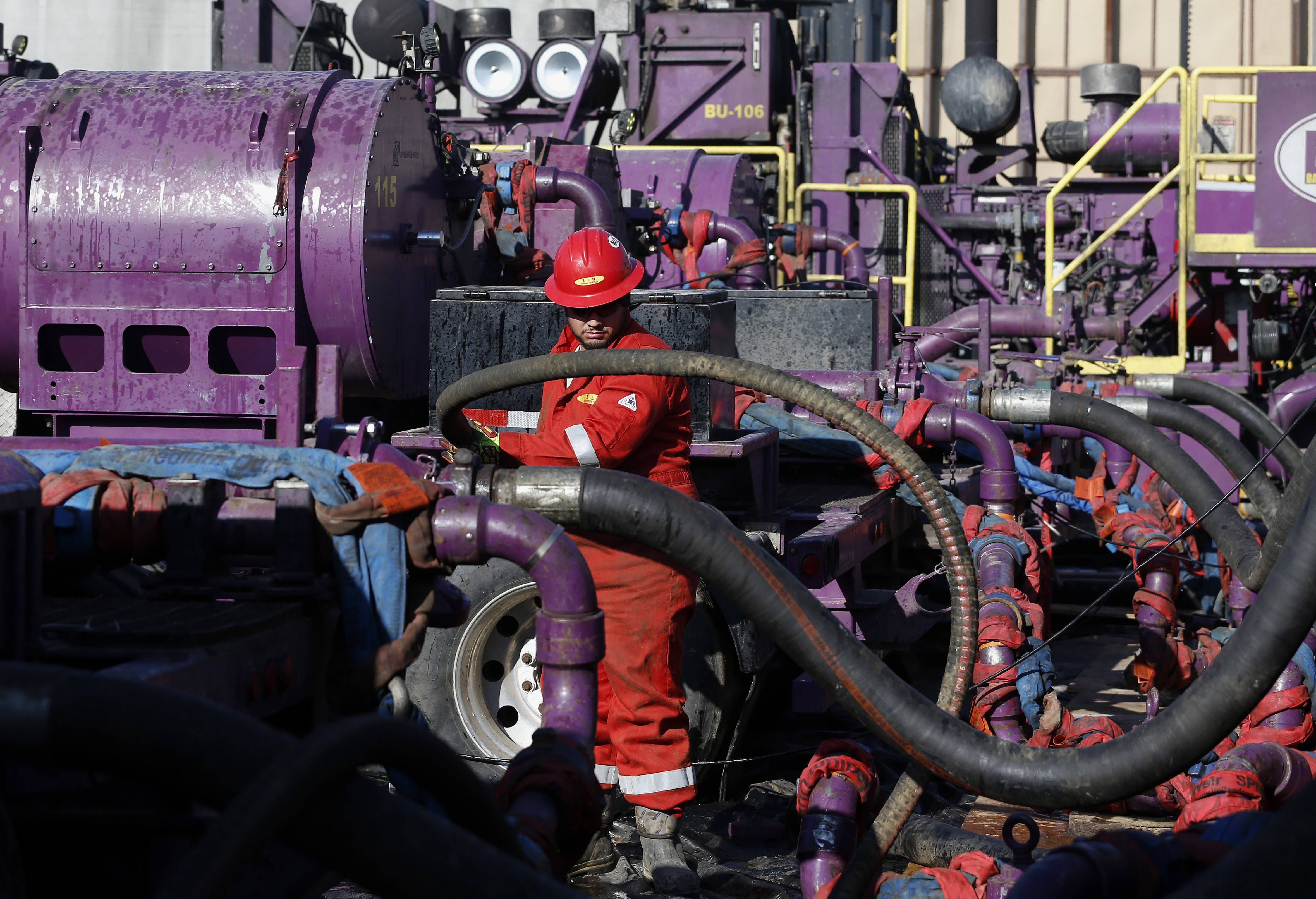 A worker adjusts hoses during a hydraulic fracturing operation at an Encana Corp. gas well, near Mead, Colo.
