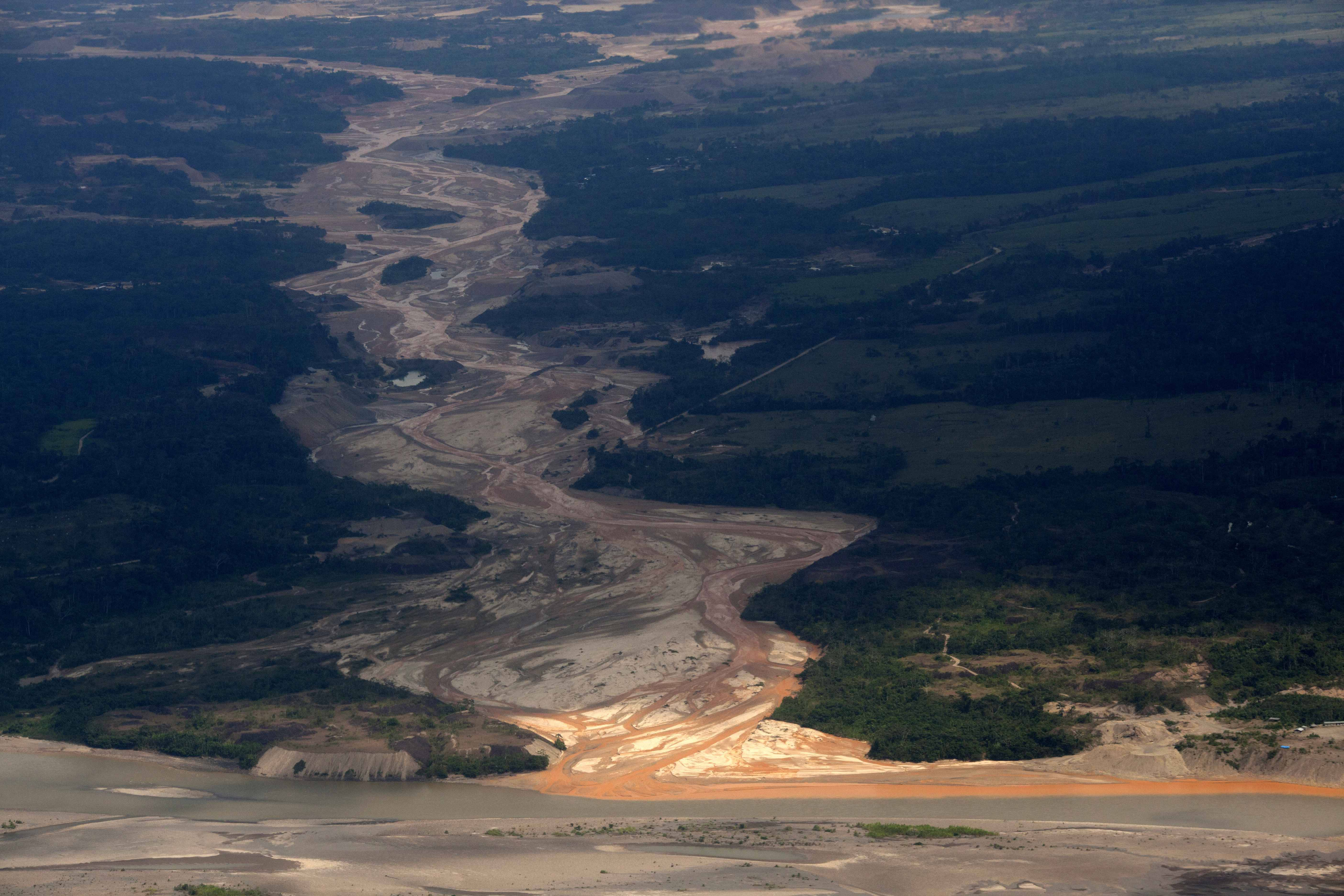 Aerial photo shows a river polluted by waste from informal mining in Peru's Madre de Dios region.