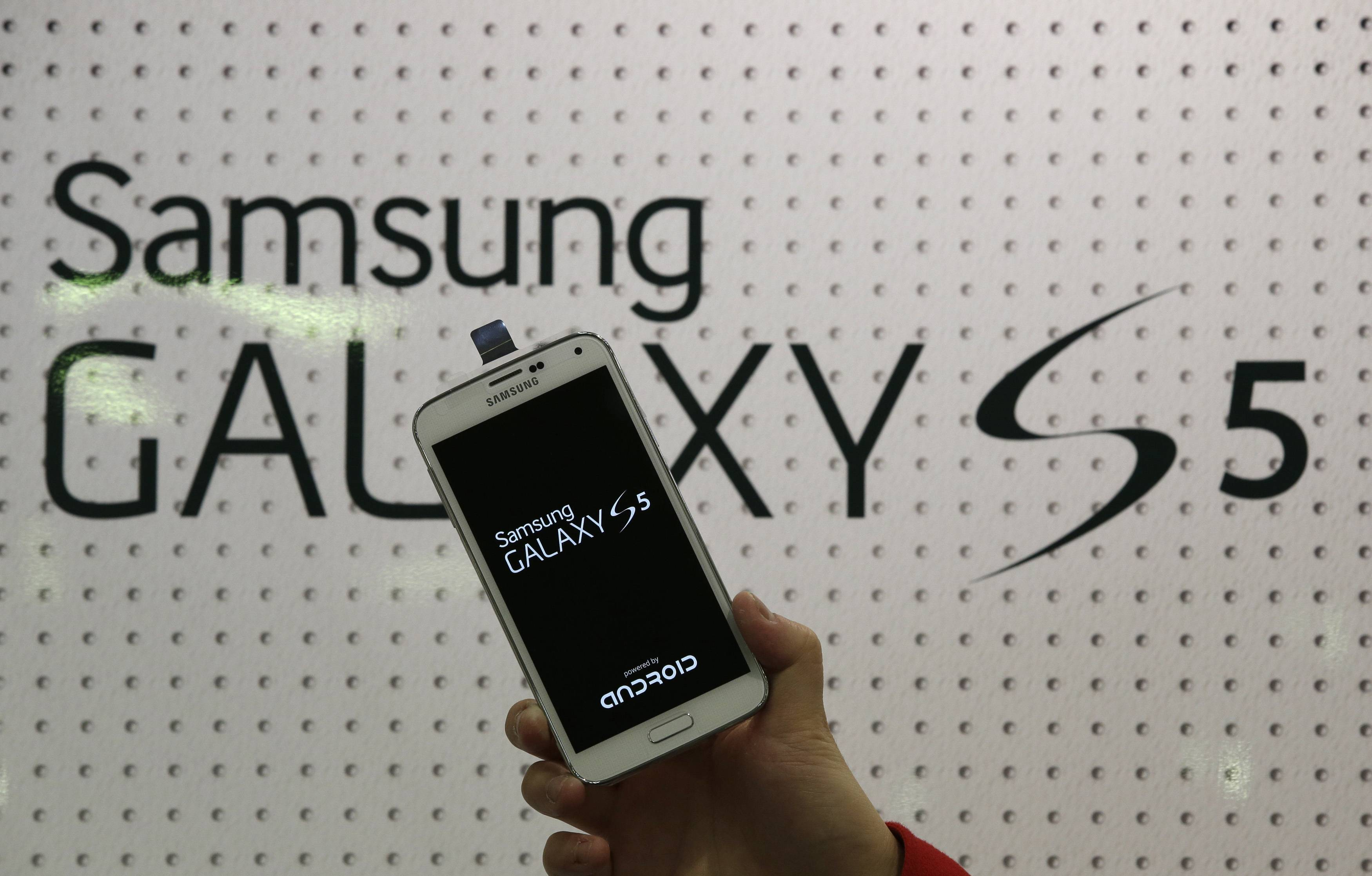 An employee shows Samsung's Galaxy S5 smartphone at a mobile phone shop in Seoul, South Korea. Samsung's new Galaxy S5 smartphone is more durable than last year's model and other leading Android phones, but the iPhone 5s outperformed all of them in part because of its smaller size, a new study finds.