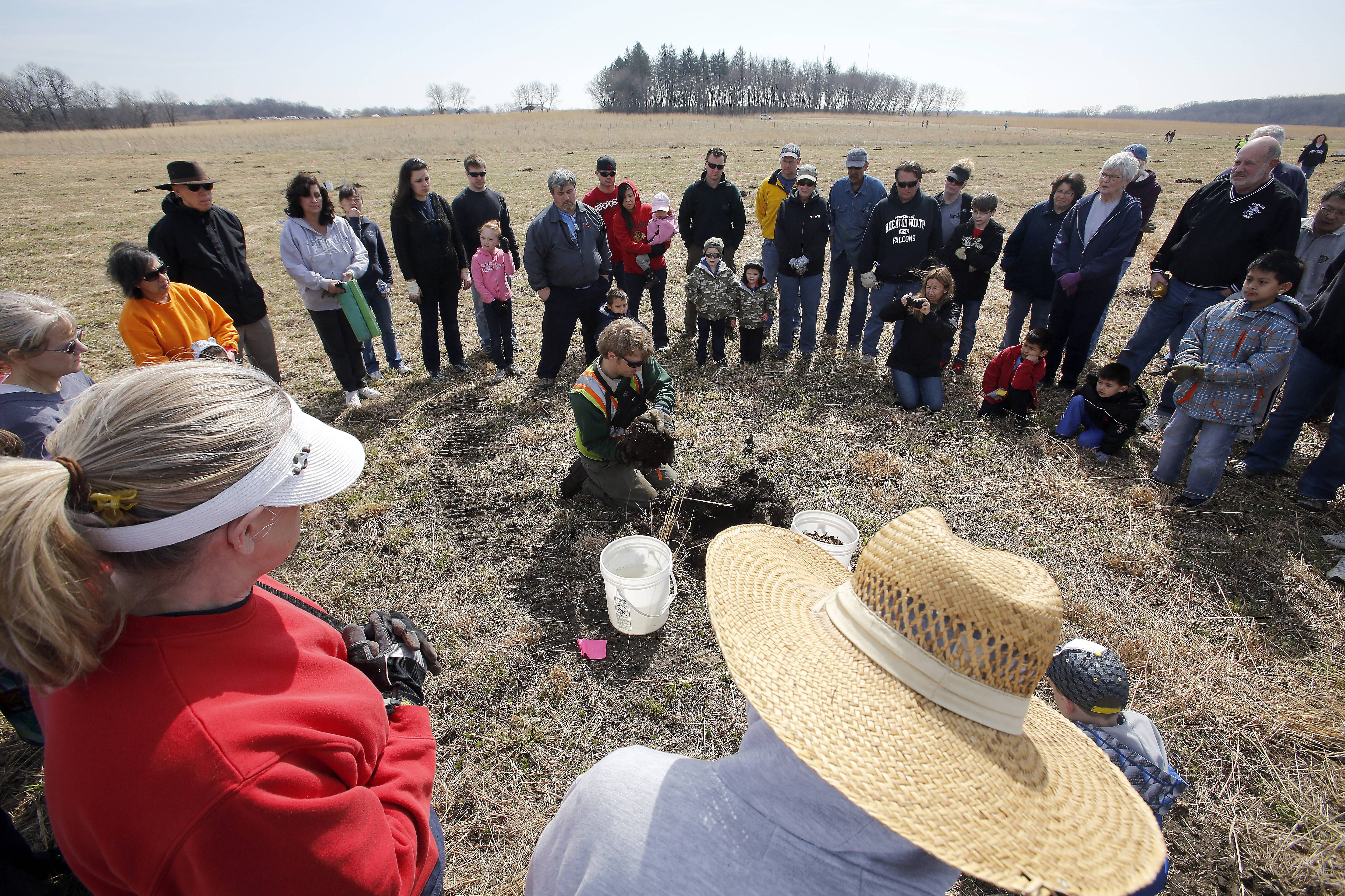 Andy Olnas, a restoration technician with the Kane County Forest Preserve District, shows a group of people how to properly plant a tree. Hundreds of volunteers ventured into Fitchie Creek Forest Preserve in Elgin Saturday to plant some 400 trees in honor of Earth Day.