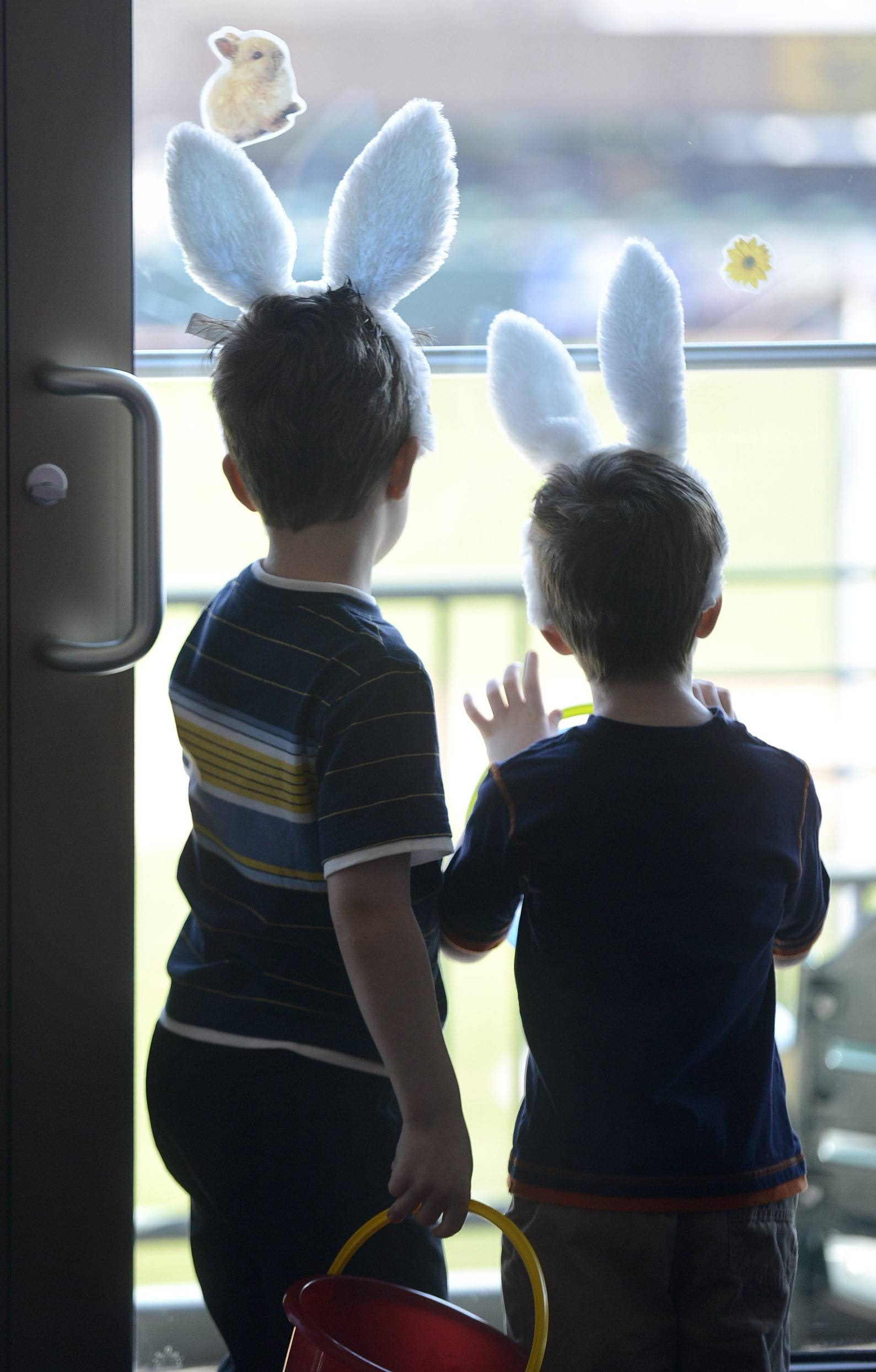Jackson Karlovsky, 6, left, and his brother, Finnegan, 4, of Algonquin look out onto a ballfield filled with eggs at the Kane County Cougars Easter breakfast at Fifth Third Bank Ballpark in Geneva on Saturday. The two-hour breakfast concluded with an Easter egg hunt.