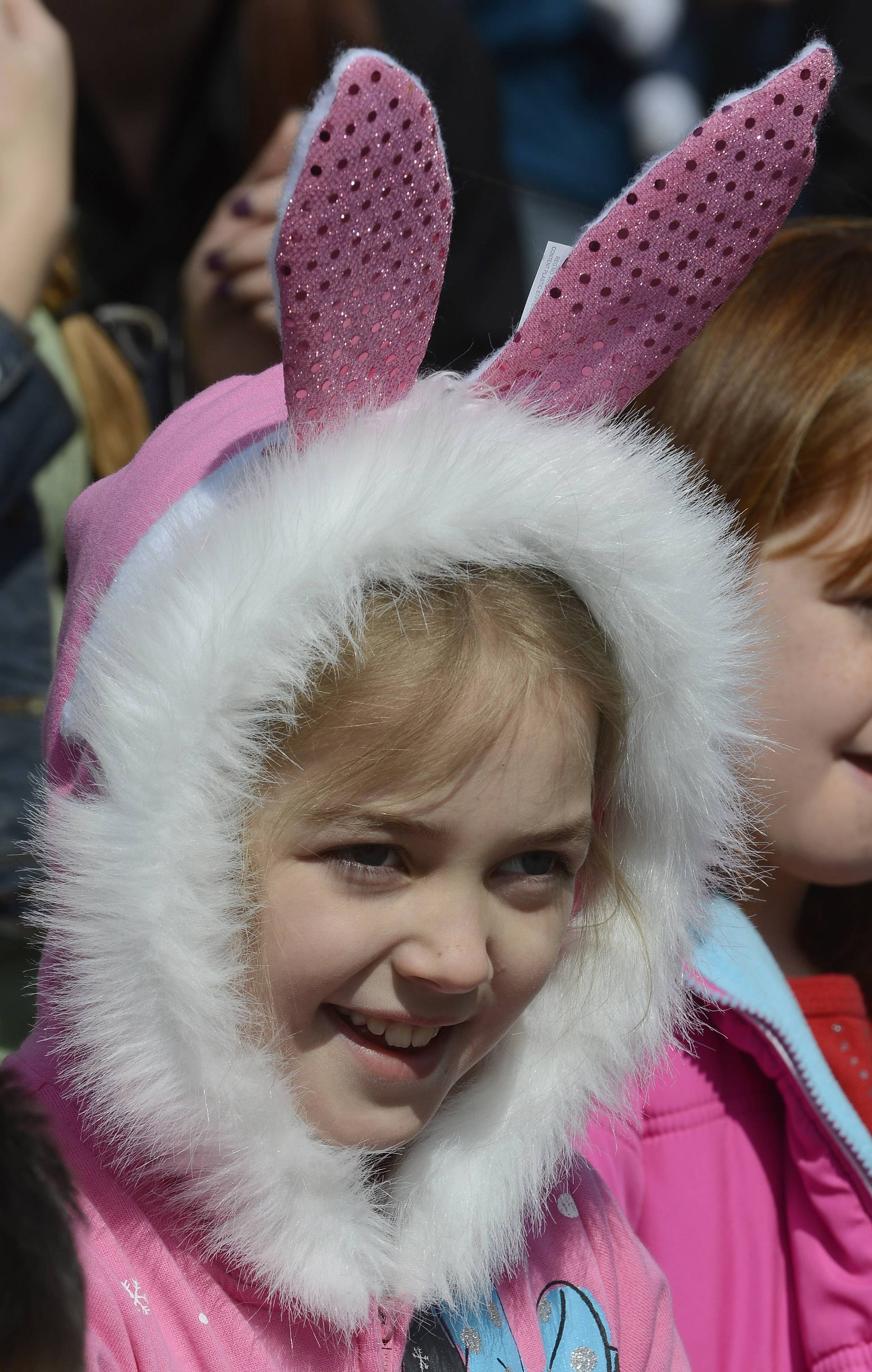 Megan Greenhill, 8, of Trevor, Wis., watches as Saturday's Easter Parade approaches on Main Street in Antioch.