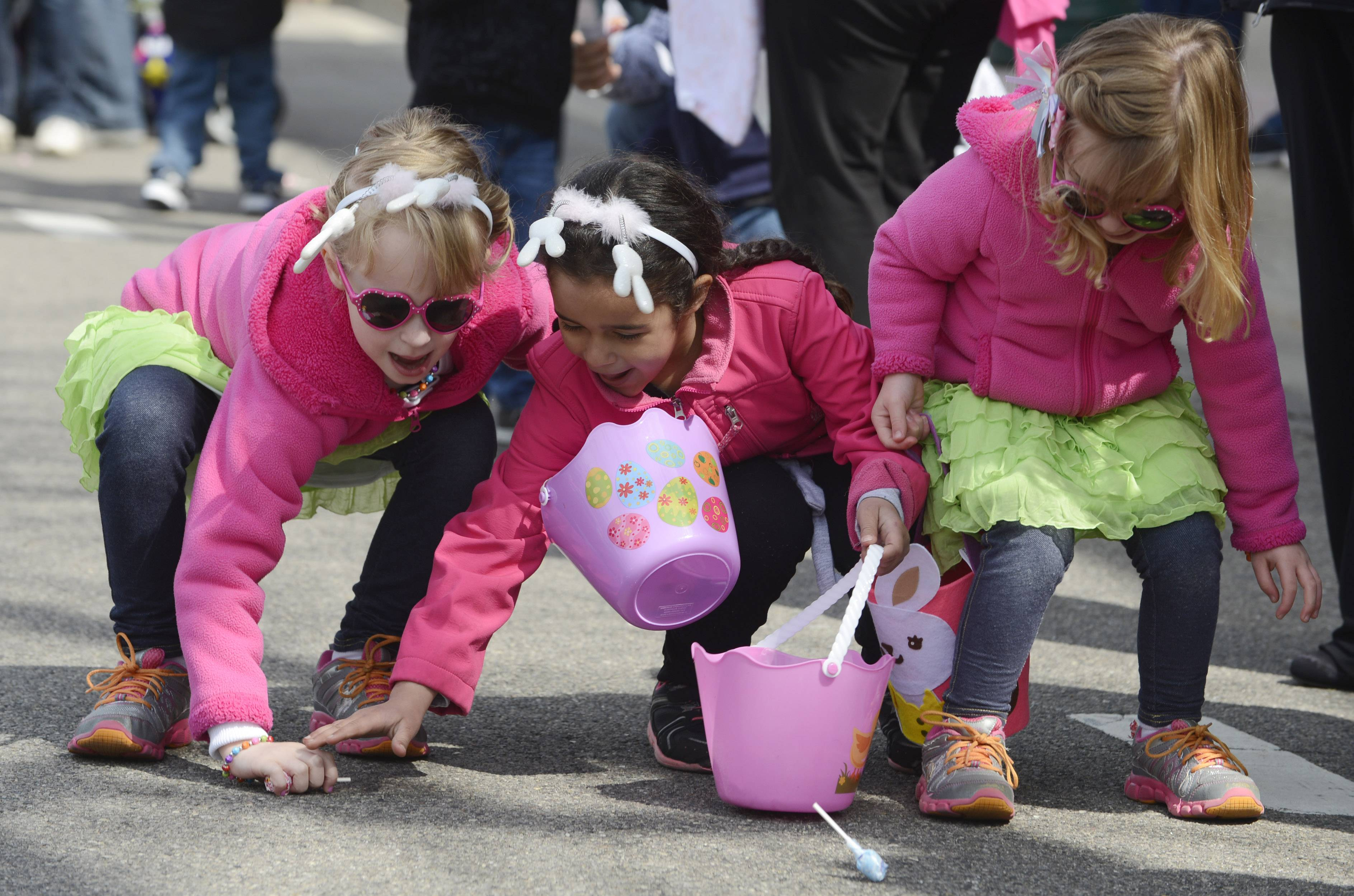 Aubrey Burgart, 6, of Antioch, left, her sister, Annabelle, 3, right, and their friend Isabella Lebron, 6, of Lake Villa gather candy during Saturday's Easter parade on Main Street in Antioch.