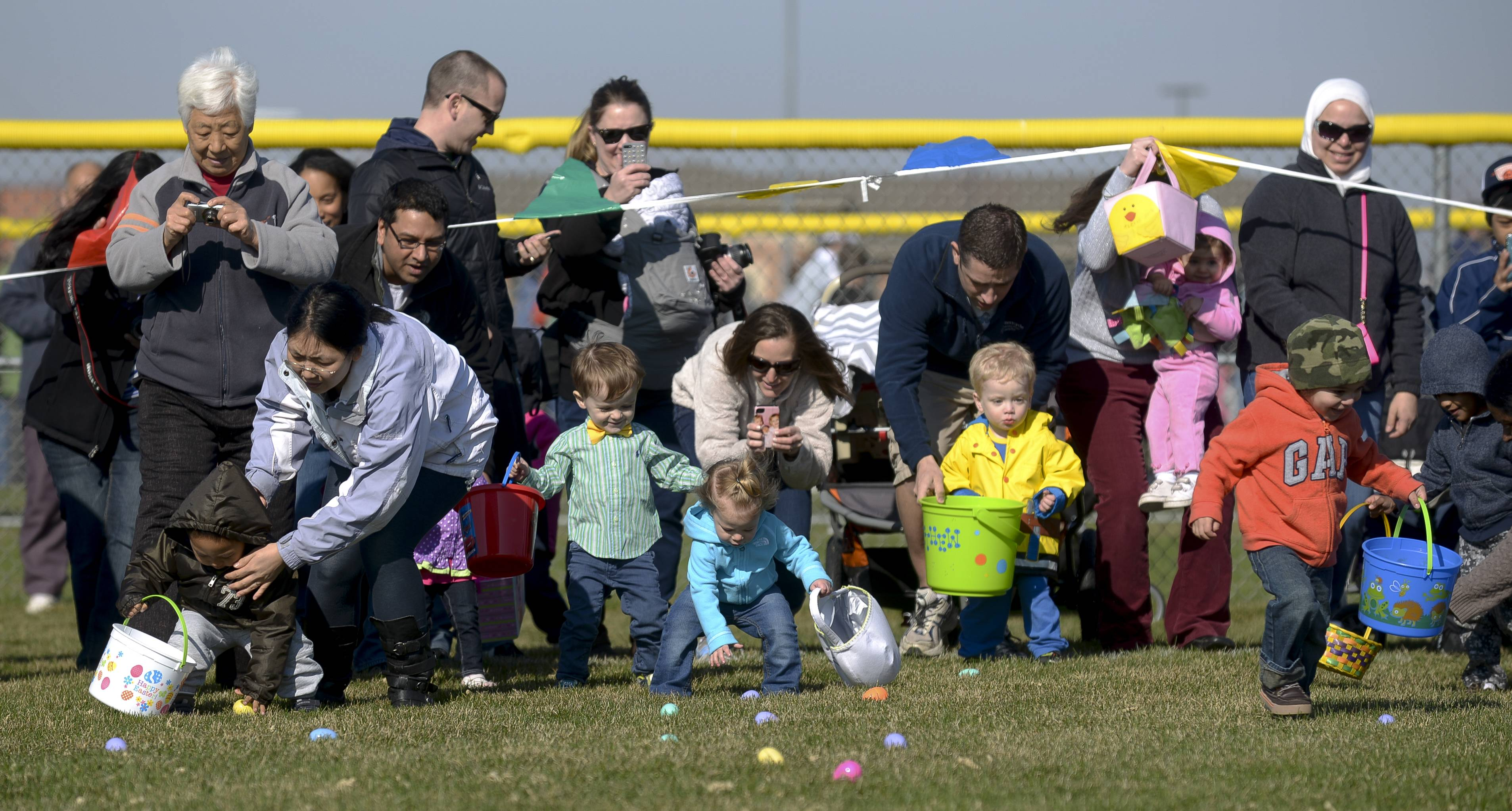 Children and parents scramble for eggs in the 0-2 field of the 29th annual Jaycees egg hunt at the Frontier Sports Complex in Naperville.