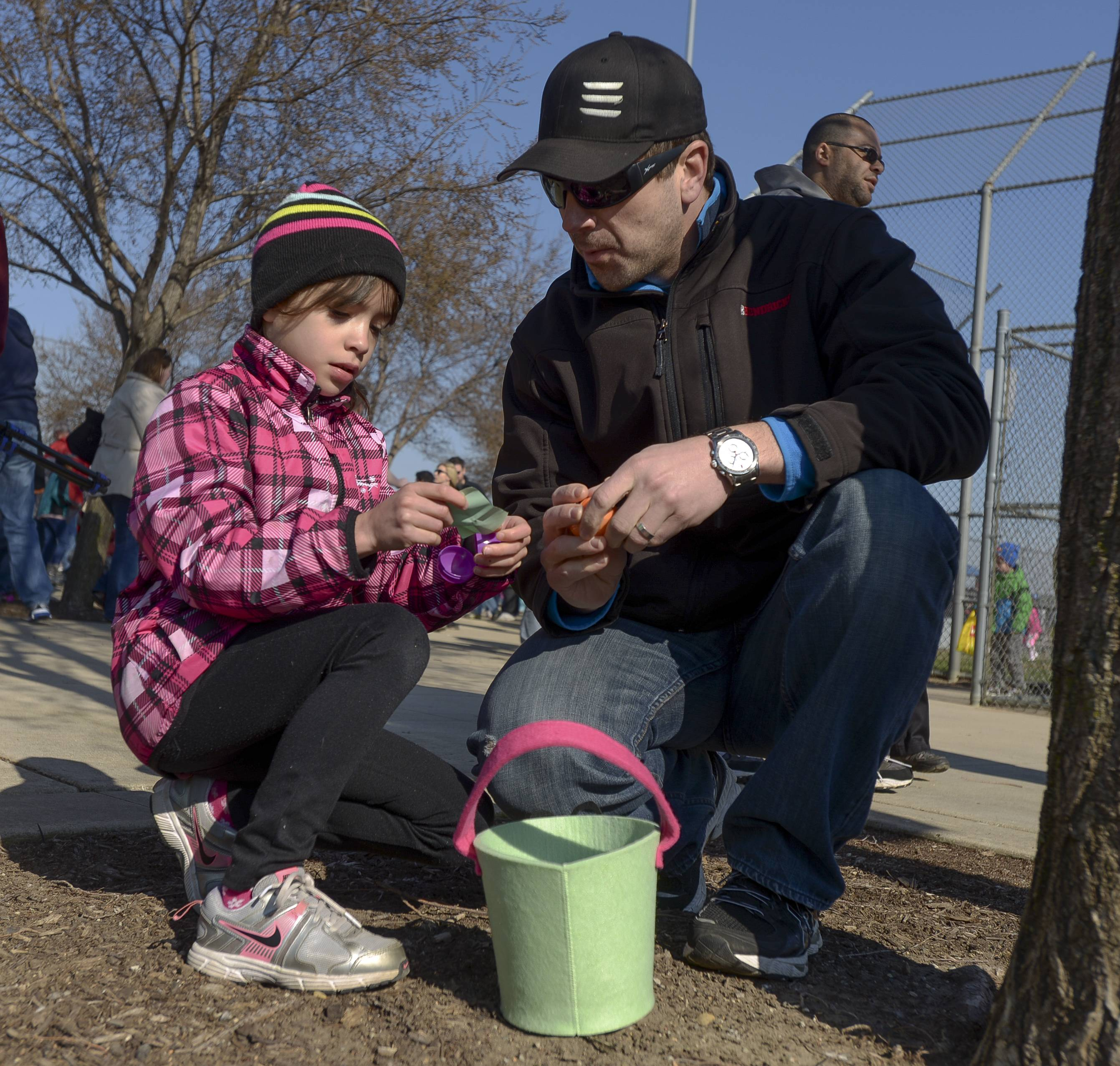 "Addie Batsch, 6, of Naperville shows her father Chris she picked one of the ""Golden Ticket"" eggs, winning her a larger prize during the 29th annual Jaycees egg hunt held Saturday at the Frontier Sports Complex in Naperville."