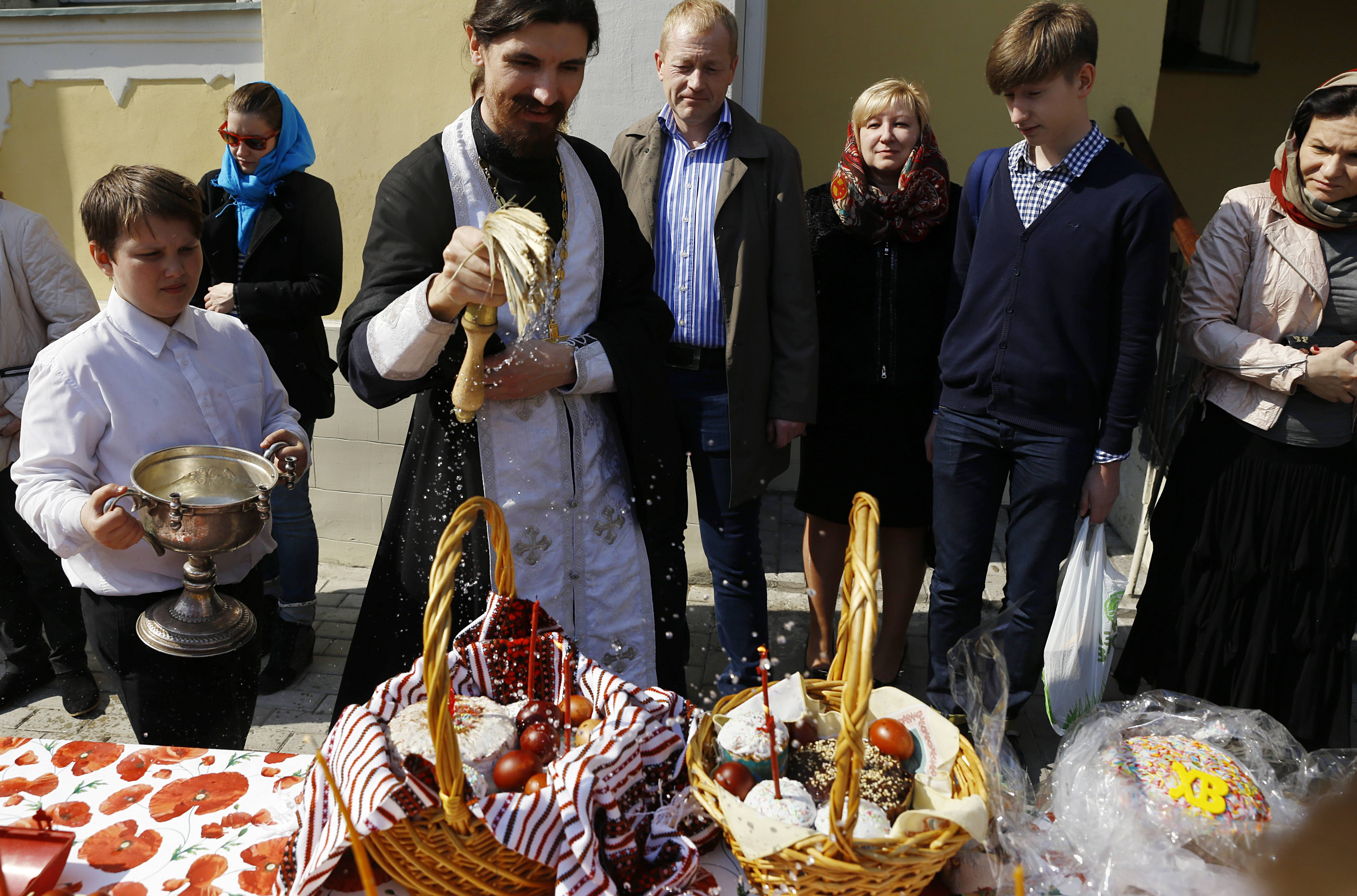 A Russian Orthodox priest blesses traditional Easter cakes and painted eggs prepared for an Easter celebration, at a church in Moscow, Russia, Saturday, April 19.