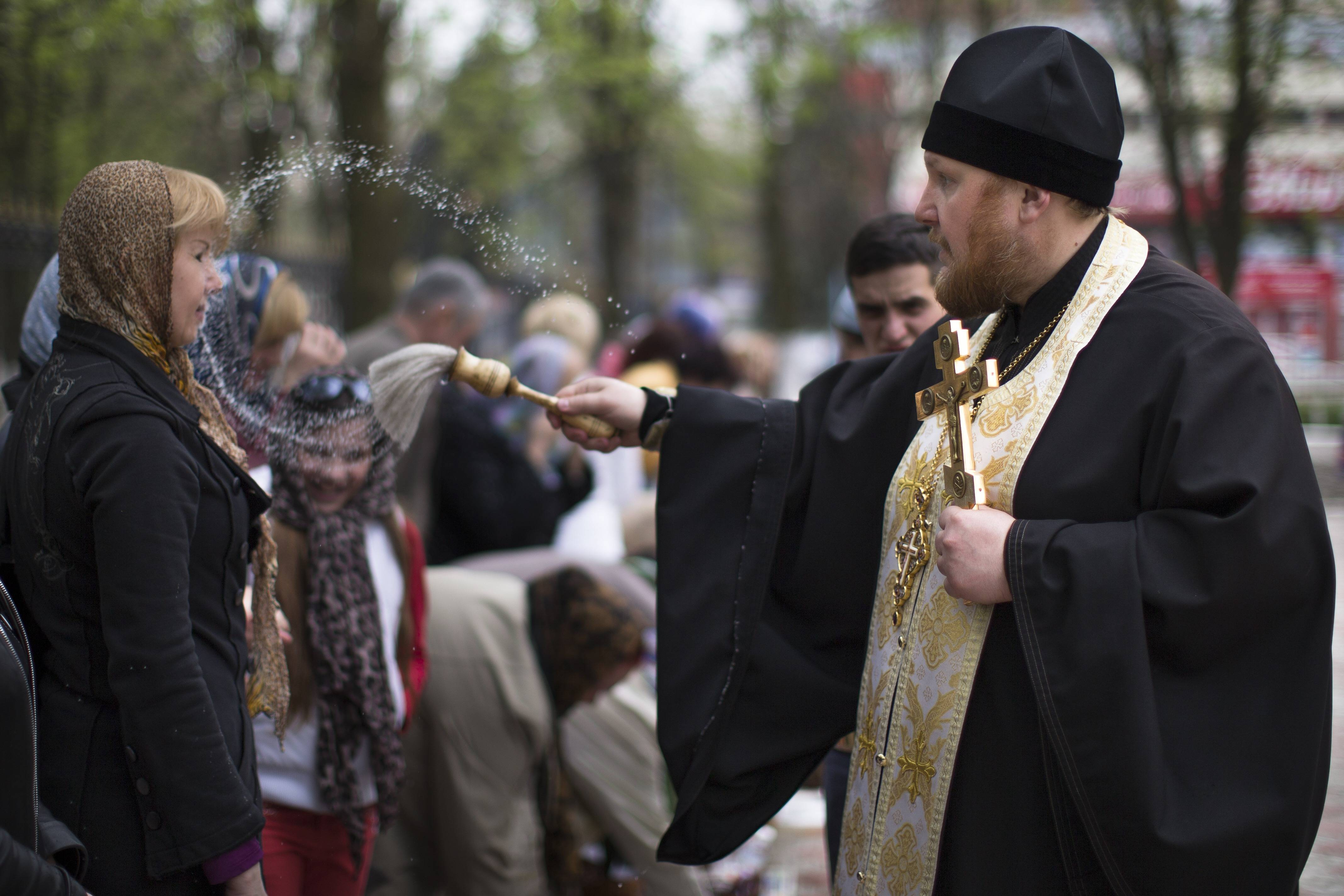 An Orthodox priest blesses a woman and traditional Easter cakes and painted eggs prepared for an Easter celebration, at a church in Slovyansk, Ukraine, Saturday, April 19. Pro-Russian insurgents defiantly refused Friday to surrender their weapons or give up government buildings in eastern Ukraine, despite a diplomatic accord reached in Geneva and overtures from the government in Kiev.