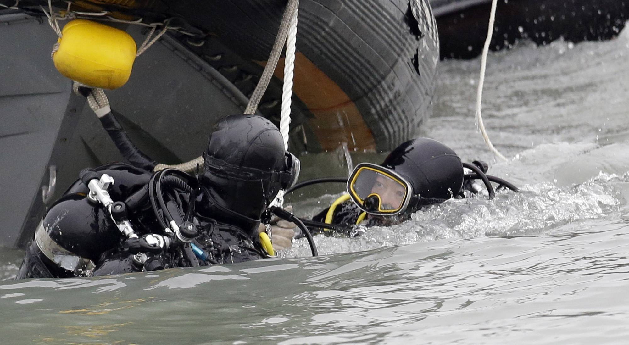 South Korean frogmen talk at each other as they search passengers of the sunken ferry Sewol off the southern coast near Jindo, south of Seoul, South Korea, Saturday, April 19. The captain of the sunken South Korean ferry was arrested Saturday on suspicion of negligence and abandoning people in need, as investigators looked into whether his evacuation order came too late to save lives. Two crew members were also arrested, a prosecutor said.