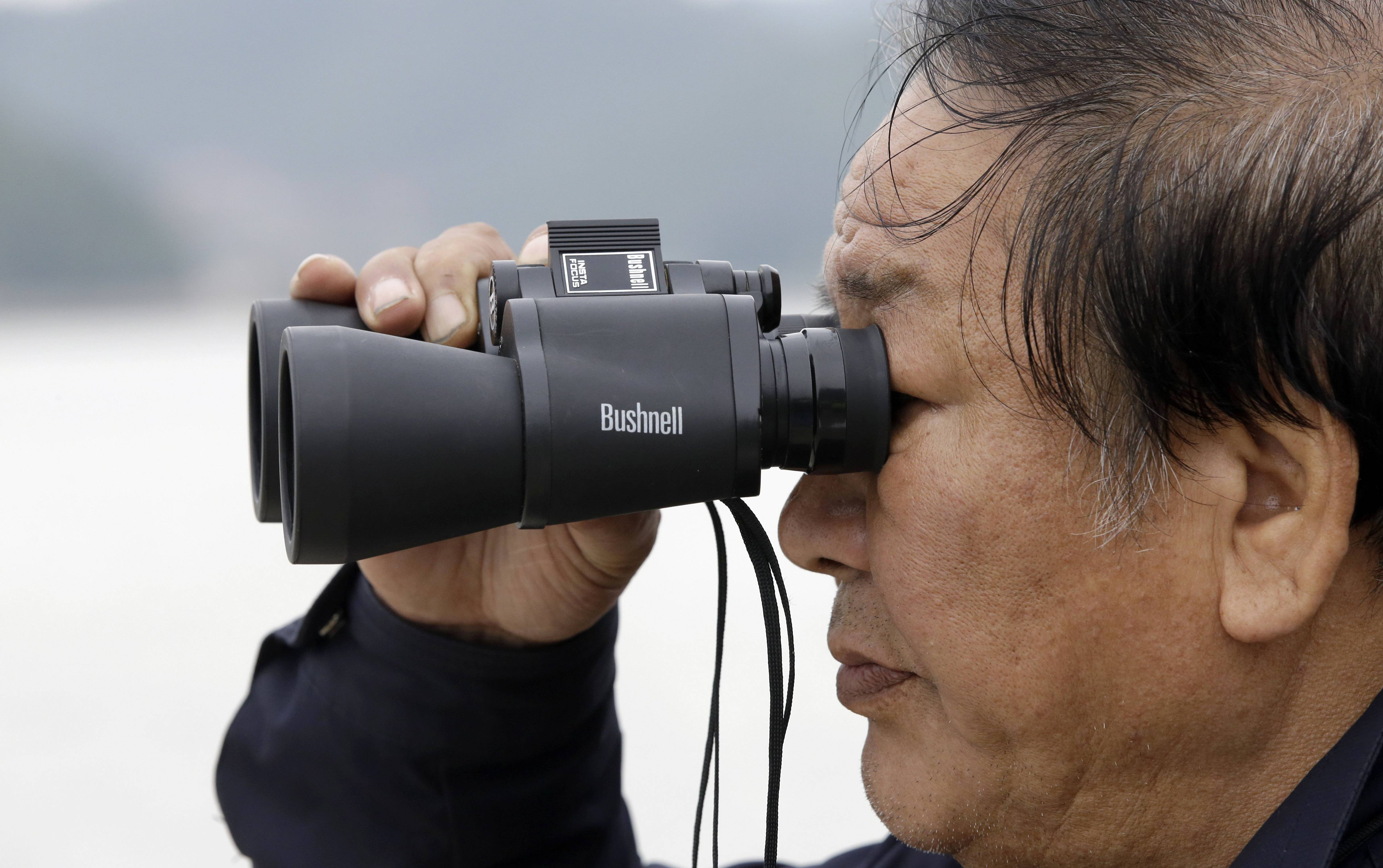 A South Korean man uses binoculars as he waits for his granddaughter who aboard the sunken ferry Sewol in the water off the southern coast at a port in Jindo, south of Seoul, South Korea, Saturday, April 19. The captain of the sunken South Korean ferry was arrested Saturday on suspicion of negligence and abandoning people in need, as investigators looked into whether his evacuation order came too late to save lives. Two crew members were also arrested, a prosecutor said.