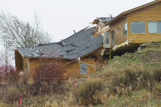 A house breaks apart as a slow-moving landslide in Jackson, Wyo. advances downhill on Friday, April 18. The slide has cut off access to a 60-person neighborhood and has threatened town utilities, including a water line.