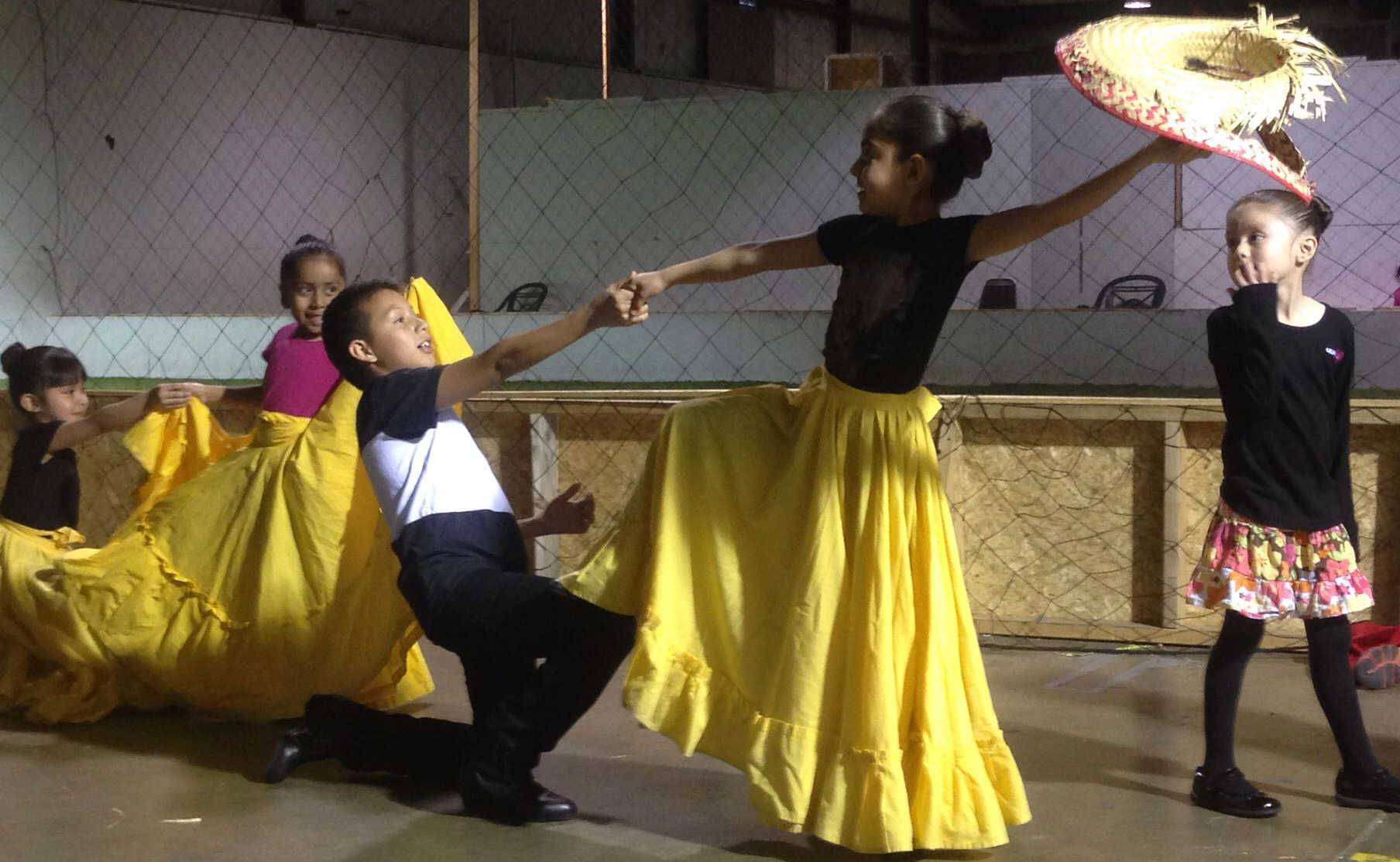 Johan Sanchez, 11, from Elgin, and Janeth Ortega, 8, from Streamwood, practice with Ballet Folklorico Girasol Thursday next to the indoor soccer court at Grand Plaza El Mesias mall in Elgin. The group hopes to find a more suitable space for practice.