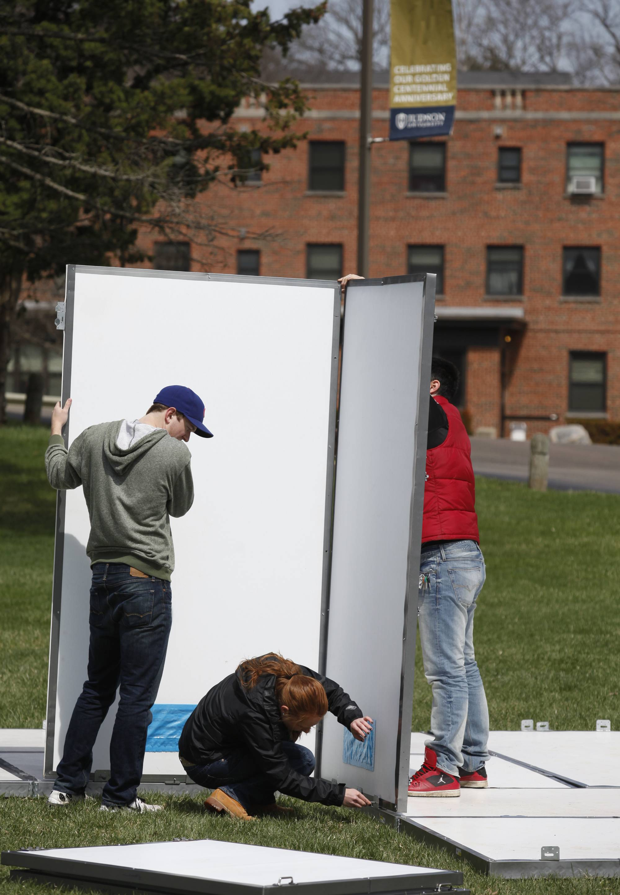 Judson University sophomore architecture students Stephen Galloway, left, Hannah Koehn and Daniel Casimiro assemble their emergency shelter during Wednesday's timed test at the Elgin campus. The students will enter three shelter designs into the Disaster Shelter Competition -- sponsored by World Vision and John Brown University -- April 24 and 25 at JBU in Arkansas.