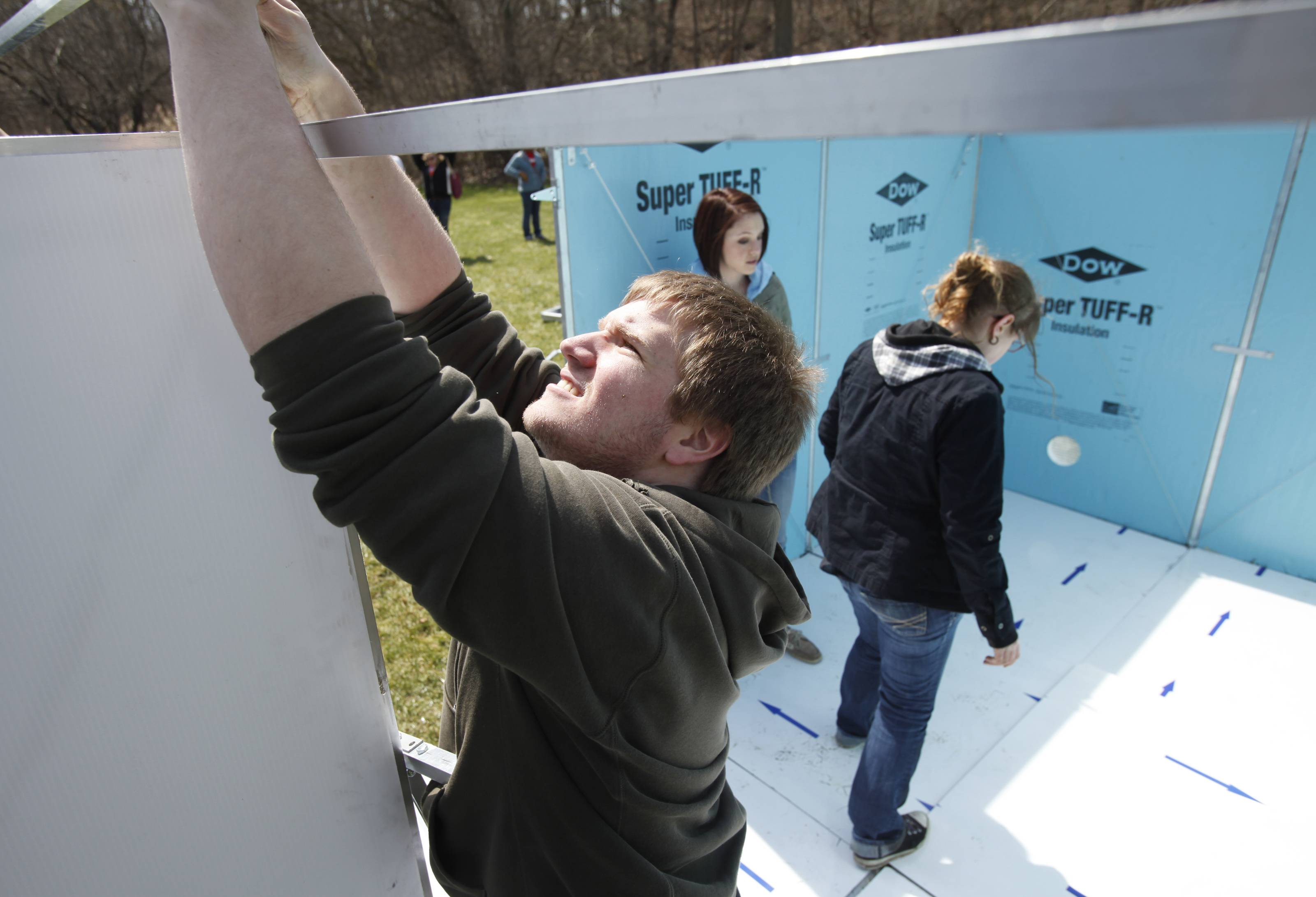 Judson University sophomore architecture student Josh Papic secures part of the support structure for his team's emergency shelter during a timed test Wednesday afternoon at the school's Elgin campus. Working behind him are fellow architecture sophomores Sarah Martinez, center, and Britteny Kitchen.