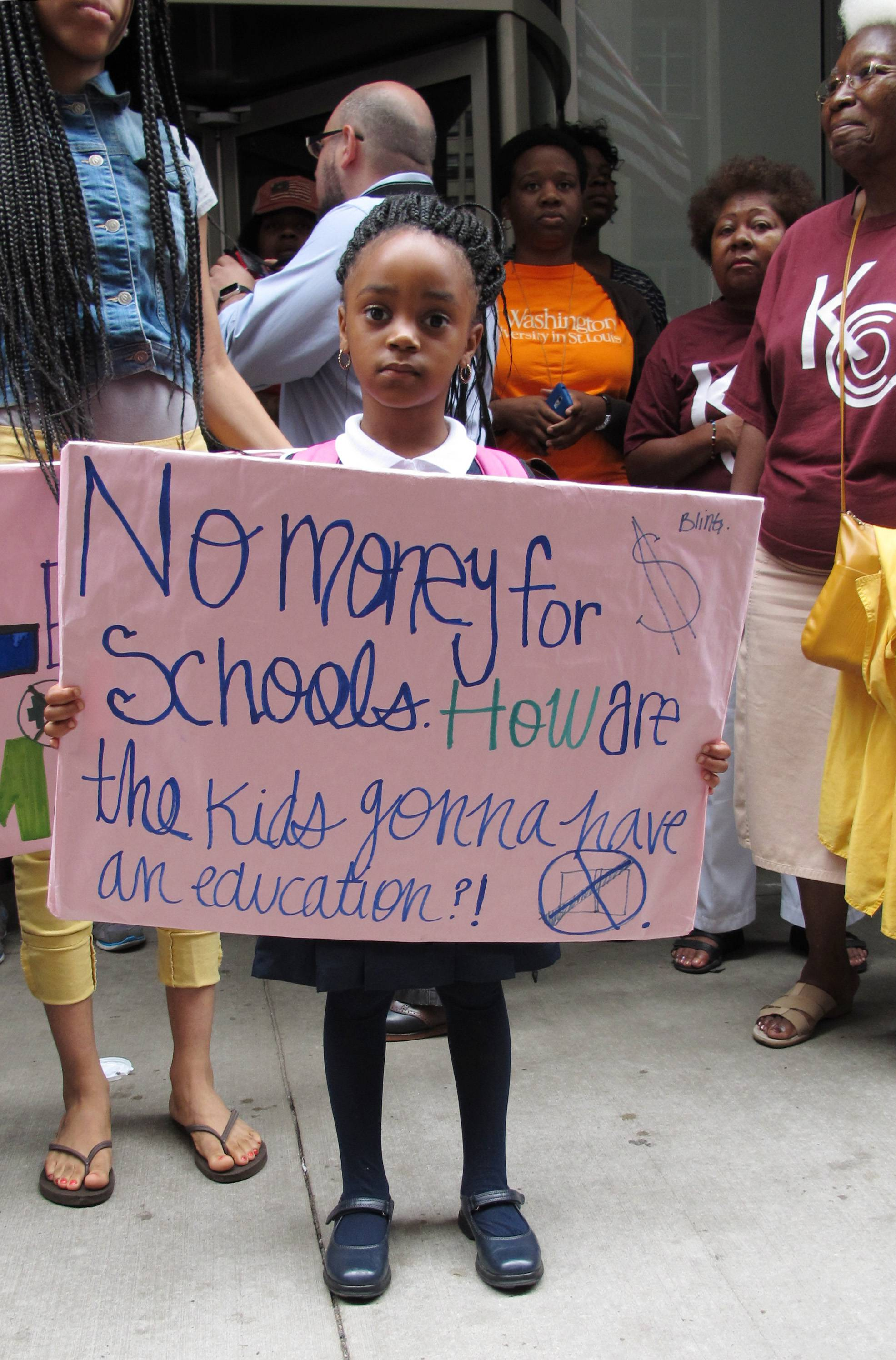 In this Aug. 28, 2013, file photo, Lariyah Beasley, a 4-year-old preschool student from Chicago, holds a sign during a rally outside the Chicago Board of Education headquarters in Chicago. Dozens of protesters, including Lariyah's mother and other parents, students and activists, decried the lack of funding for the city's public school students, especially for black students.