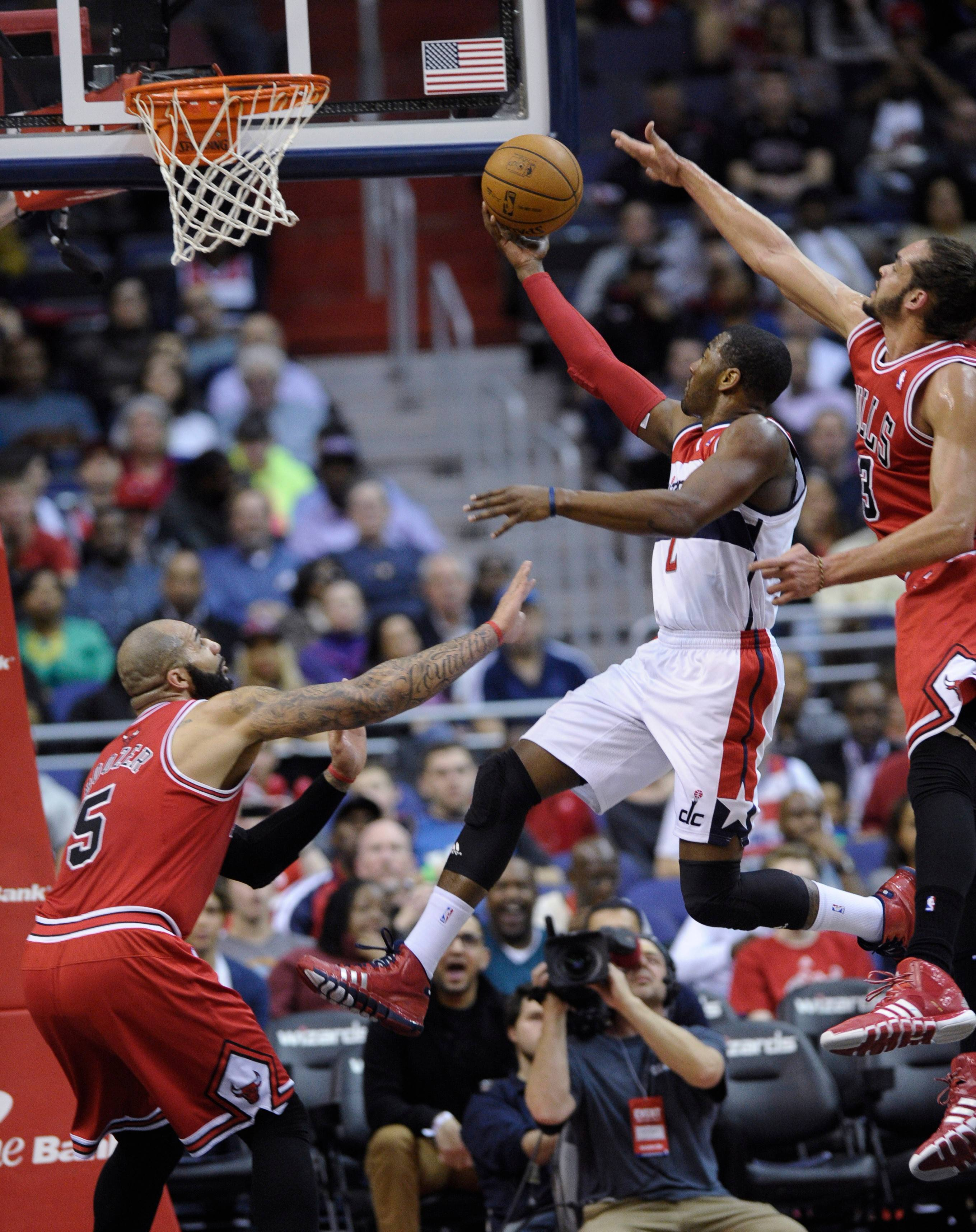 Washington Wizards guard John Wall, center, goes up for a shot under pressure from Chicago Bulls forward Carlos Boozer (5) and center Joakim Noah, right, during the first quarter of an NBA basketball game in Washington, Friday, Jan. 17, 2014.