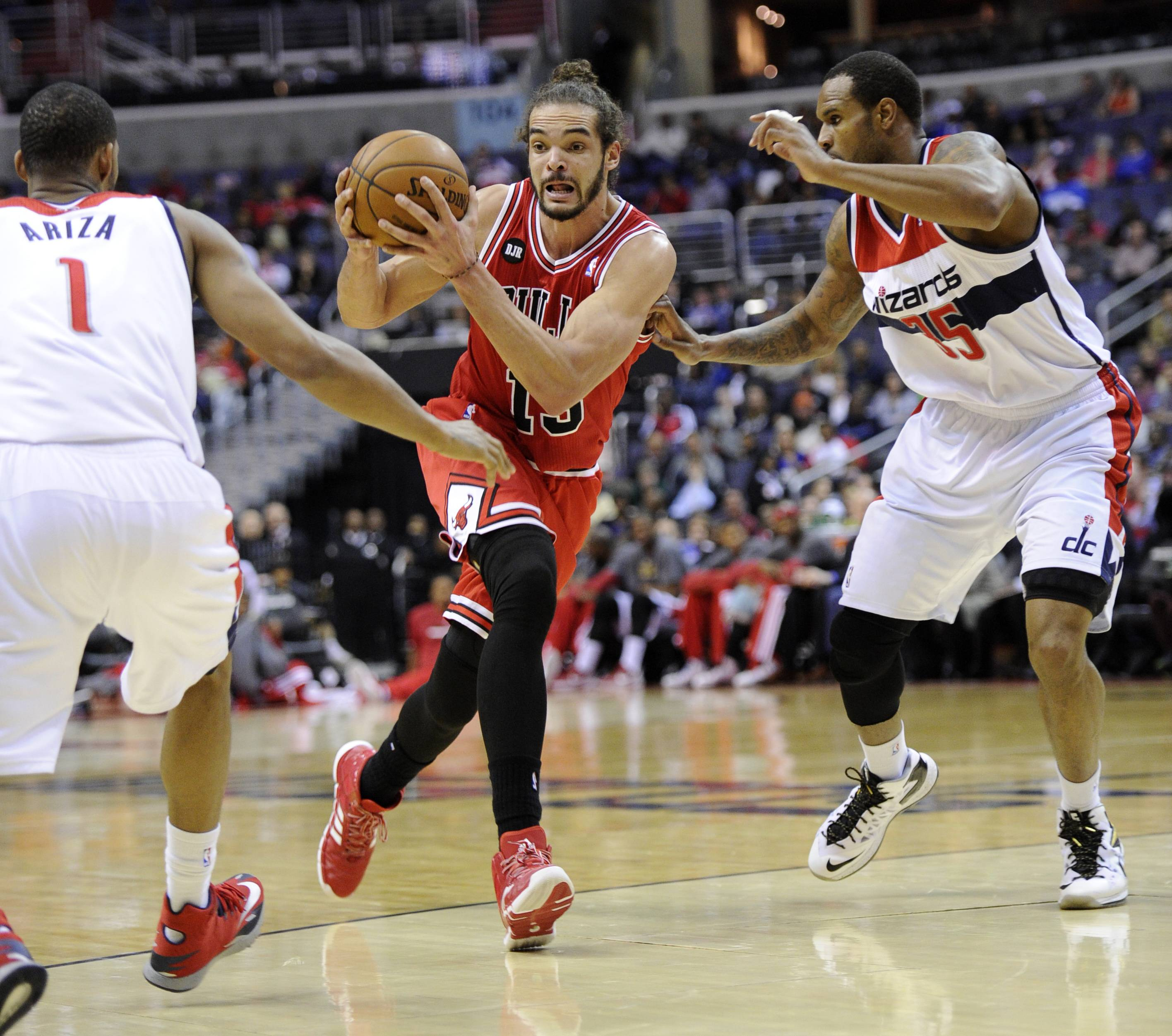 Chicago Bulls center Joakim Noah, center, drives to the basket against Washington Wizards' Trevor Ariza (1) and Trevor Booker (35) during the first half of an NBA basketball game, Saturday, April 5, 2014, in Washington.