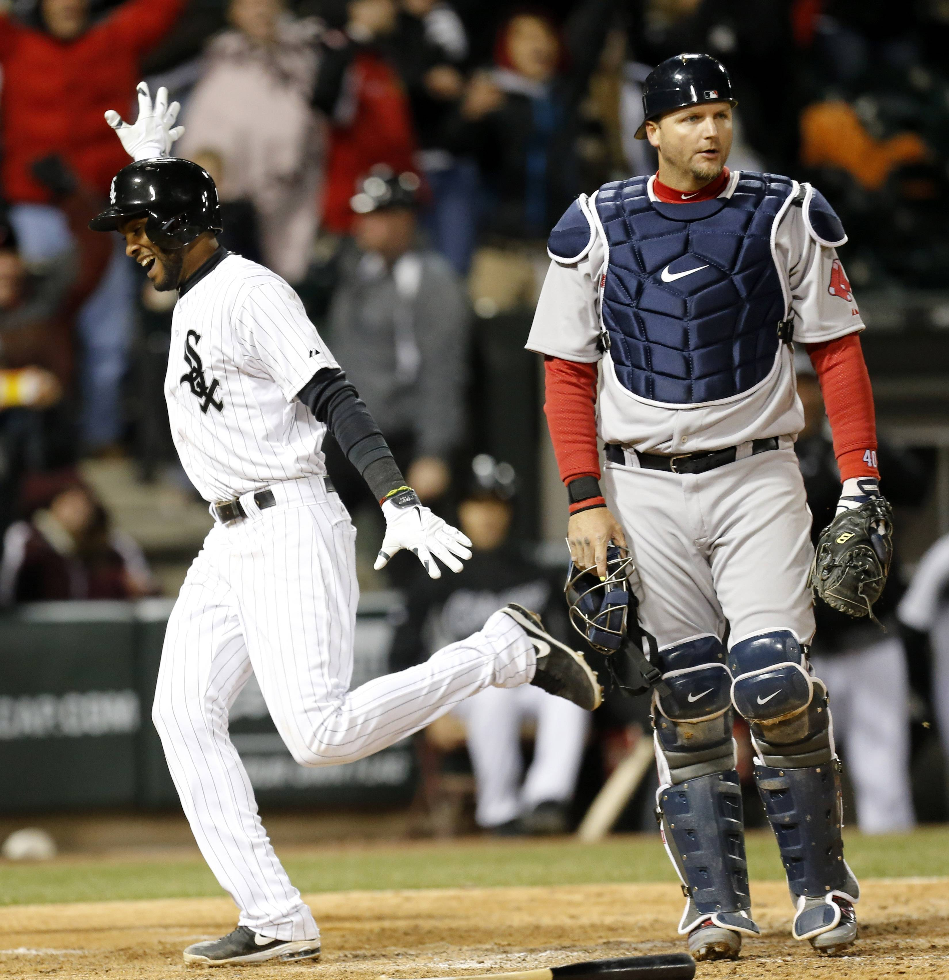 Chicago White Sox's Alexei Ramirez celebrates after scoring the game winning run off a throwing error by Boston Red Sox shortstop Xander Bogaerts as A.J. Pierzynski watches during the ninth inning of a baseball game Tuesday, April 15, 2014, in Chicago. The White Sox won 2-1.