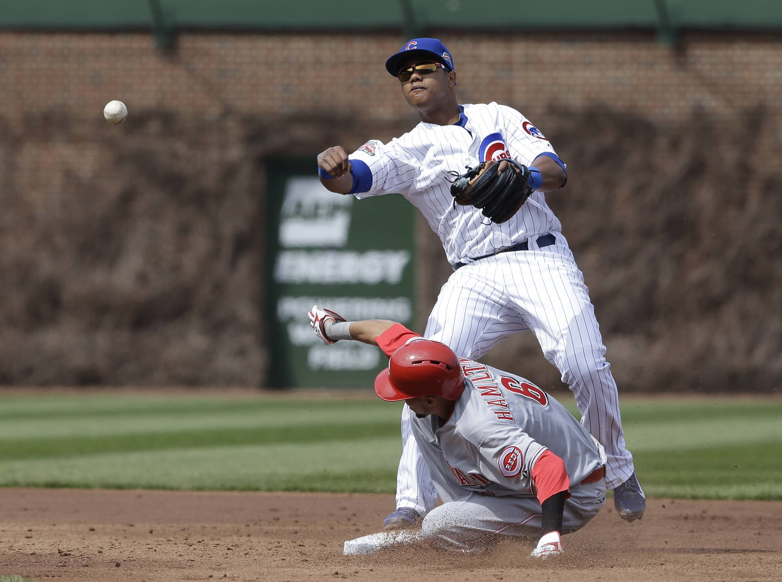 Cubs shortstop Starlin Castro, top, throws out Cincinnati Reds' Joey Votto at first base after forcing out Billy Hamilton during the third inning of a baseball game in Chicago, Saturday, April 19, 2014.