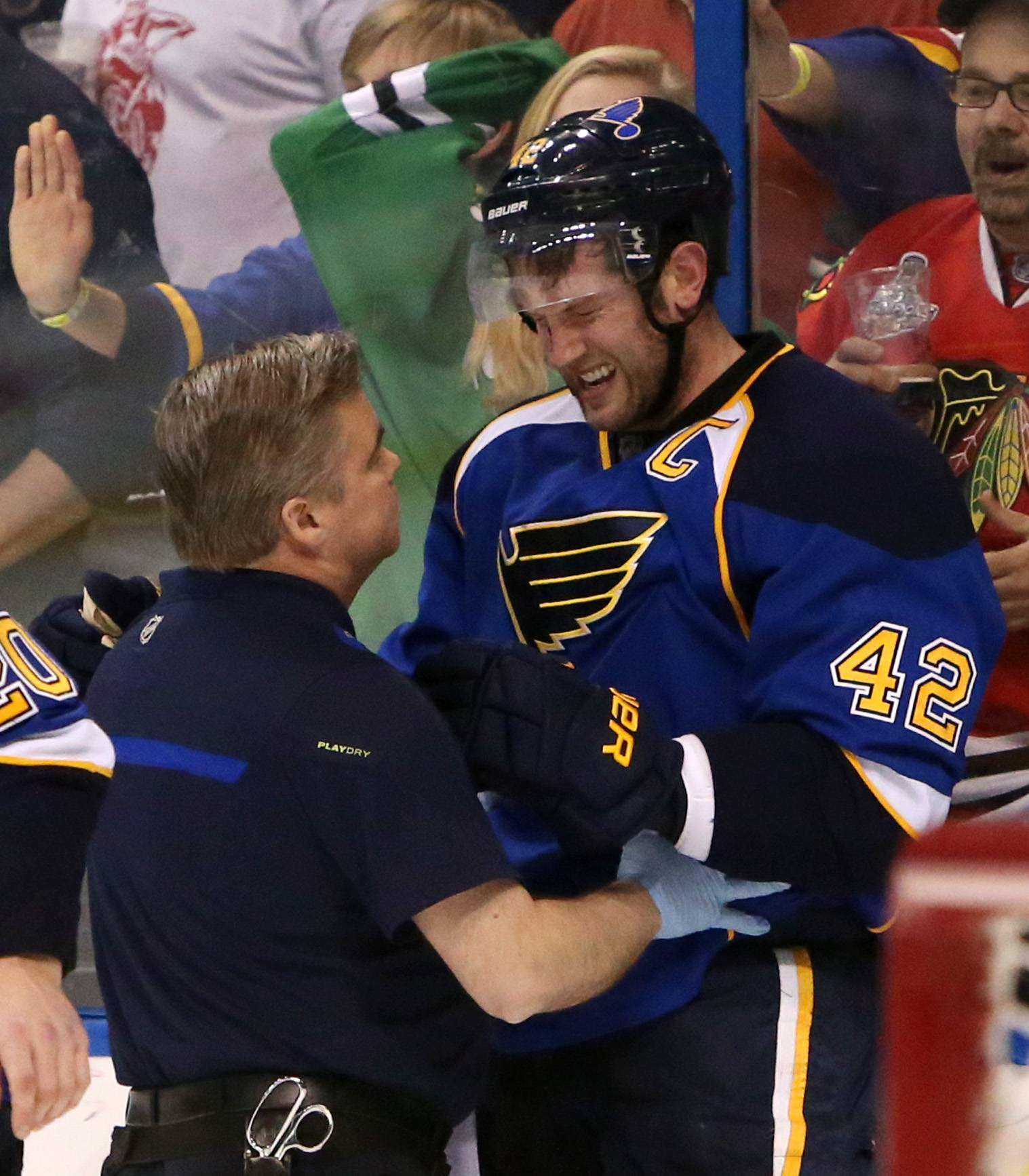 St. Louis Blues center David Backes (42) is tended to by trainer Ray Barile after taking a hit from Chicago Blackhawks defenseman Brent Seabrook in the third period during Game 2 of a first-round NHL hockey playoff series on Saturday, April 19, 2014, in St. Louis. Seabrook was assessed a game misconduct penalty for the play and the Blues scored the tying goal on the ensuing five-minute power play. Backes left the ice under his own power.