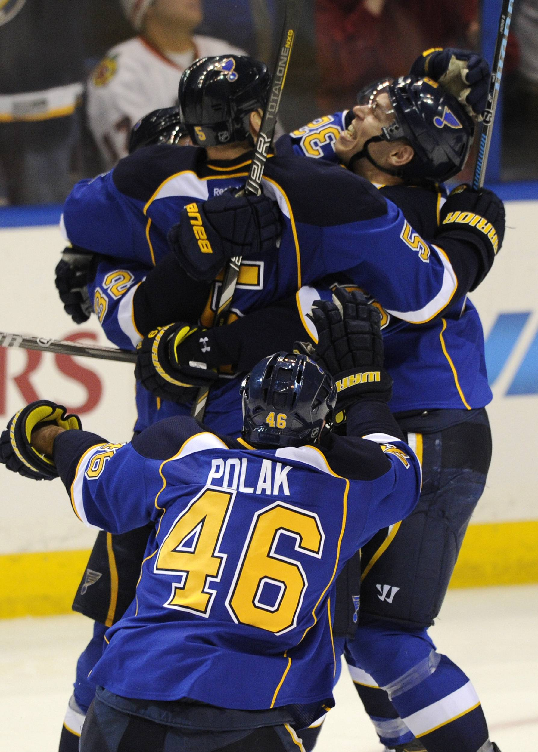 St. Louis Blues' Barret Jackman (5) is congratulated by teammates Adam Cracknell, right, and Roman Polak (46), of the Czech Republic, after his game-winning goal against the Chicago Blackhawks during overtime in Game 2 of a first-round NHL hockey playoff series, Saturday, April 19, 2014, in St. Louis.