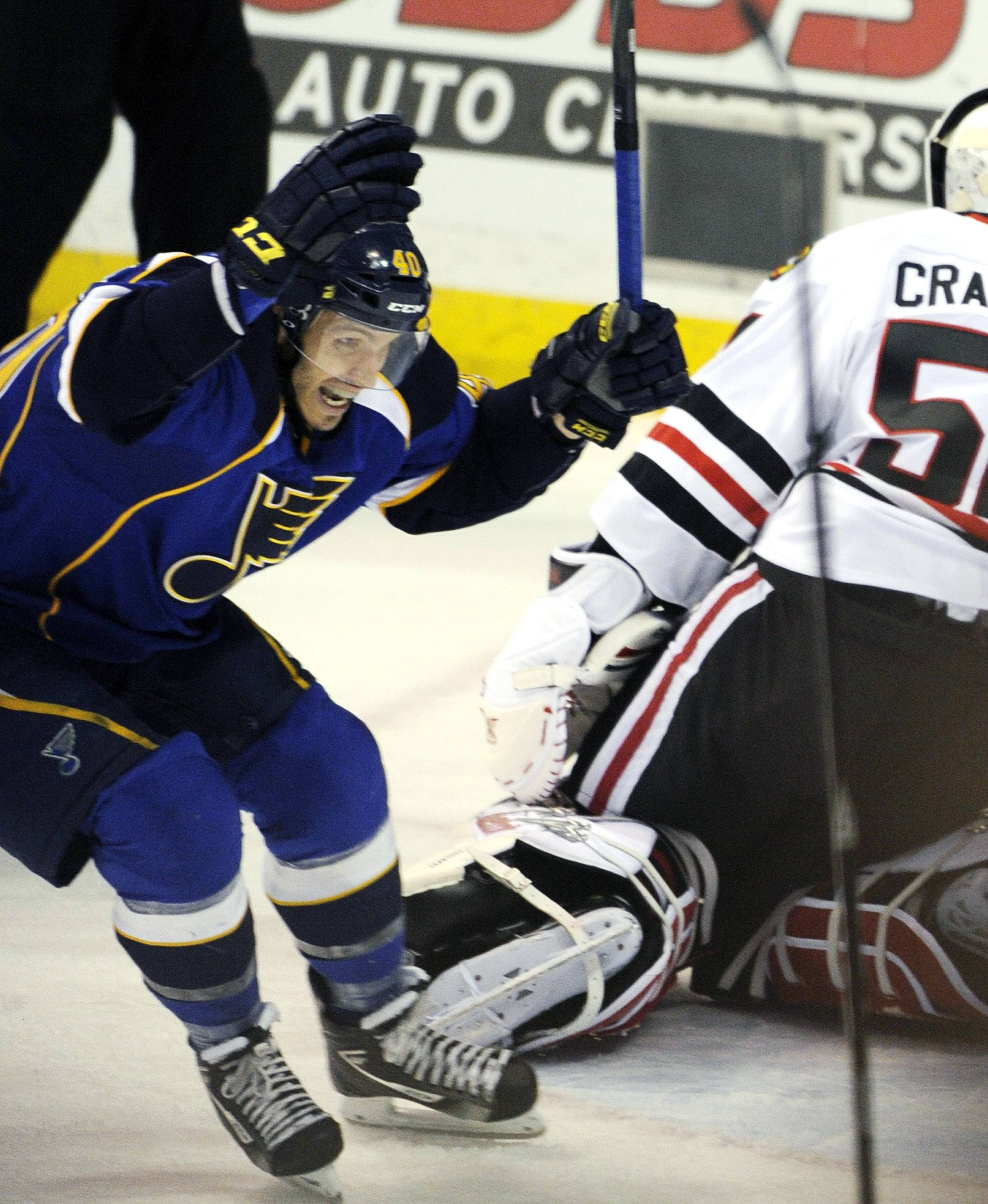 St. Louis Blues' Maxim Lapierre (40) celebrates a game-winning goal by teammate Barret Jackman as Chicago Blackhawks' goalie Corey Crawford, right, looks away during overtime in Game 2 of a first-round NHL hockey playoff series, Saturday, April 19, 2014, in St. Louis.