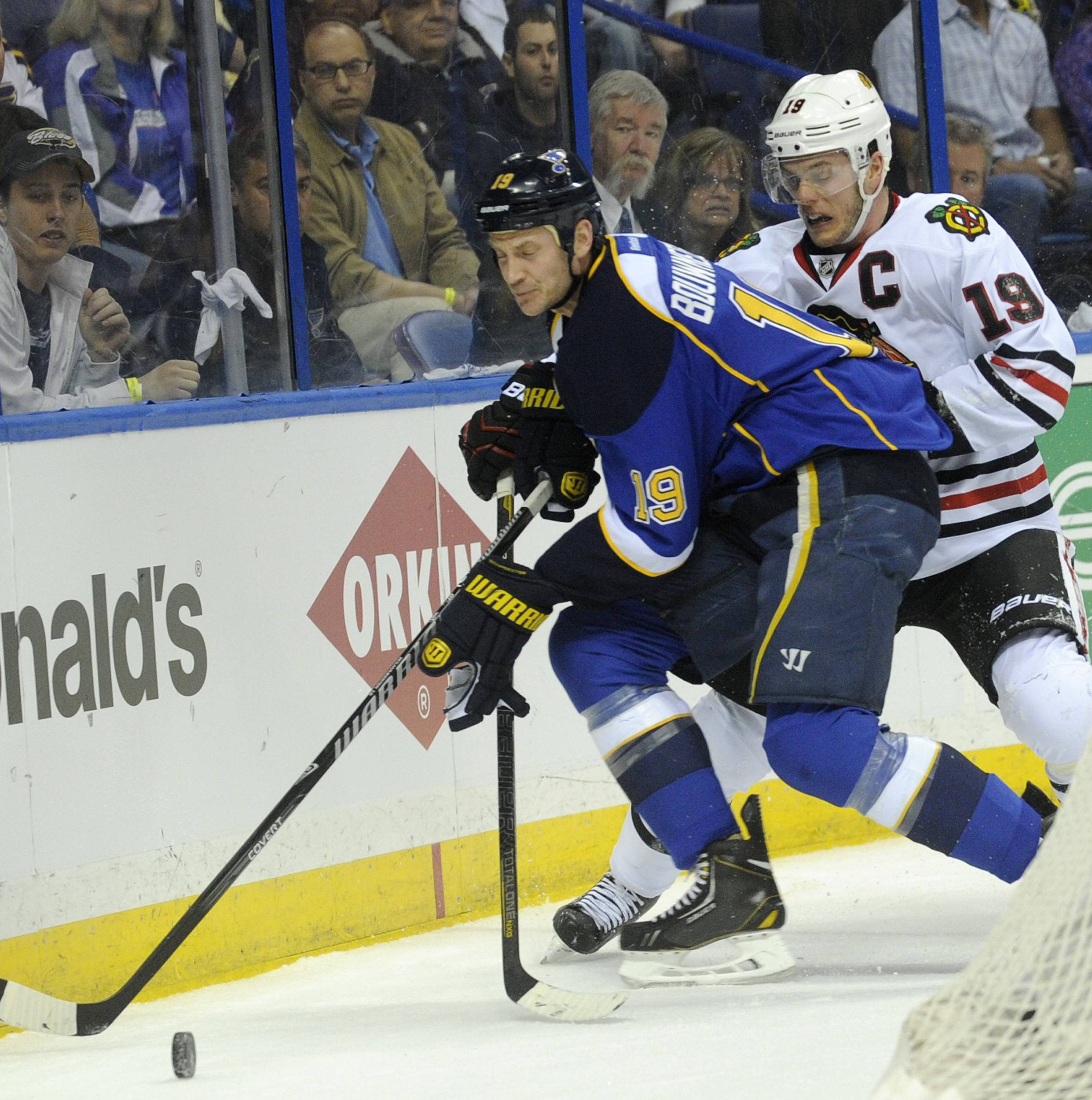 St. Louis Blues' Jay Bouwmeester, left, and Chicago Blackhawks' Jonathan Toews, right, battle for the puck during the first period in Game 2 of a first-round NHL hockey playoff series on Saturday, April 19, 2014, in St. Louis.