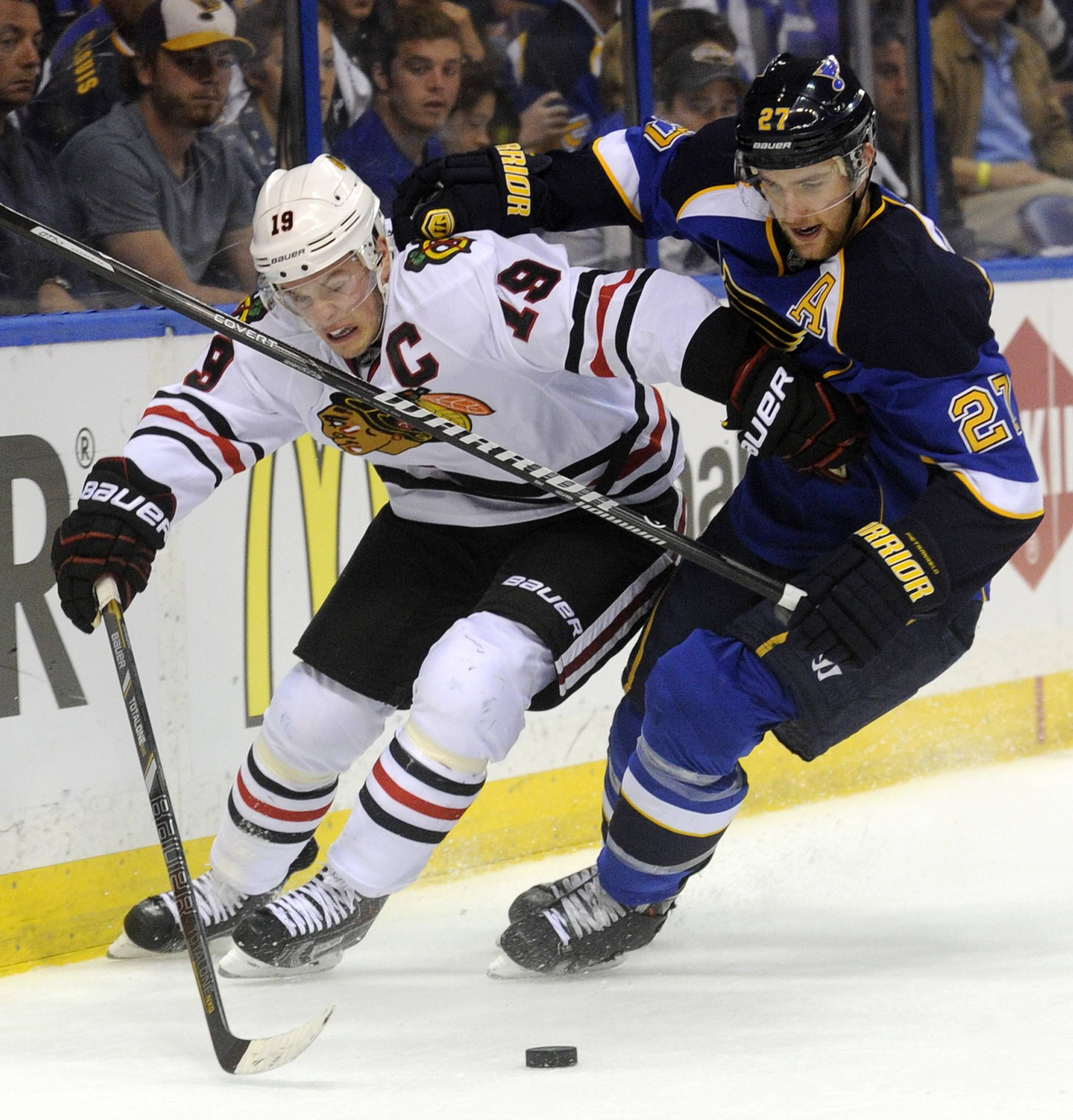 St. Louis Blues' Alex Pietrangelo (27) and Chicago Blackhawks' Jonathan Toews (19) battle for the puck during the first period in Game 2 of a first-round NHL hockey playoff series, Saturday, April 19, 2014, in St. Louis.