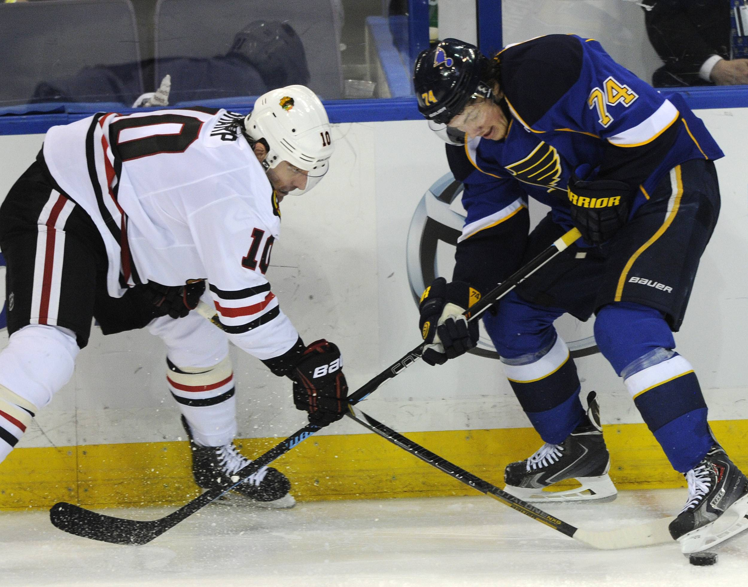 St. Louis Blues' T.J. Oshie (74) and Chicago Blackhawks' Patrick Sharp (10) reach for the puck during the second period in Game 2 of a first-round NHL hockey playoff series on Saturday, April 19, 2014, in St. Louis.