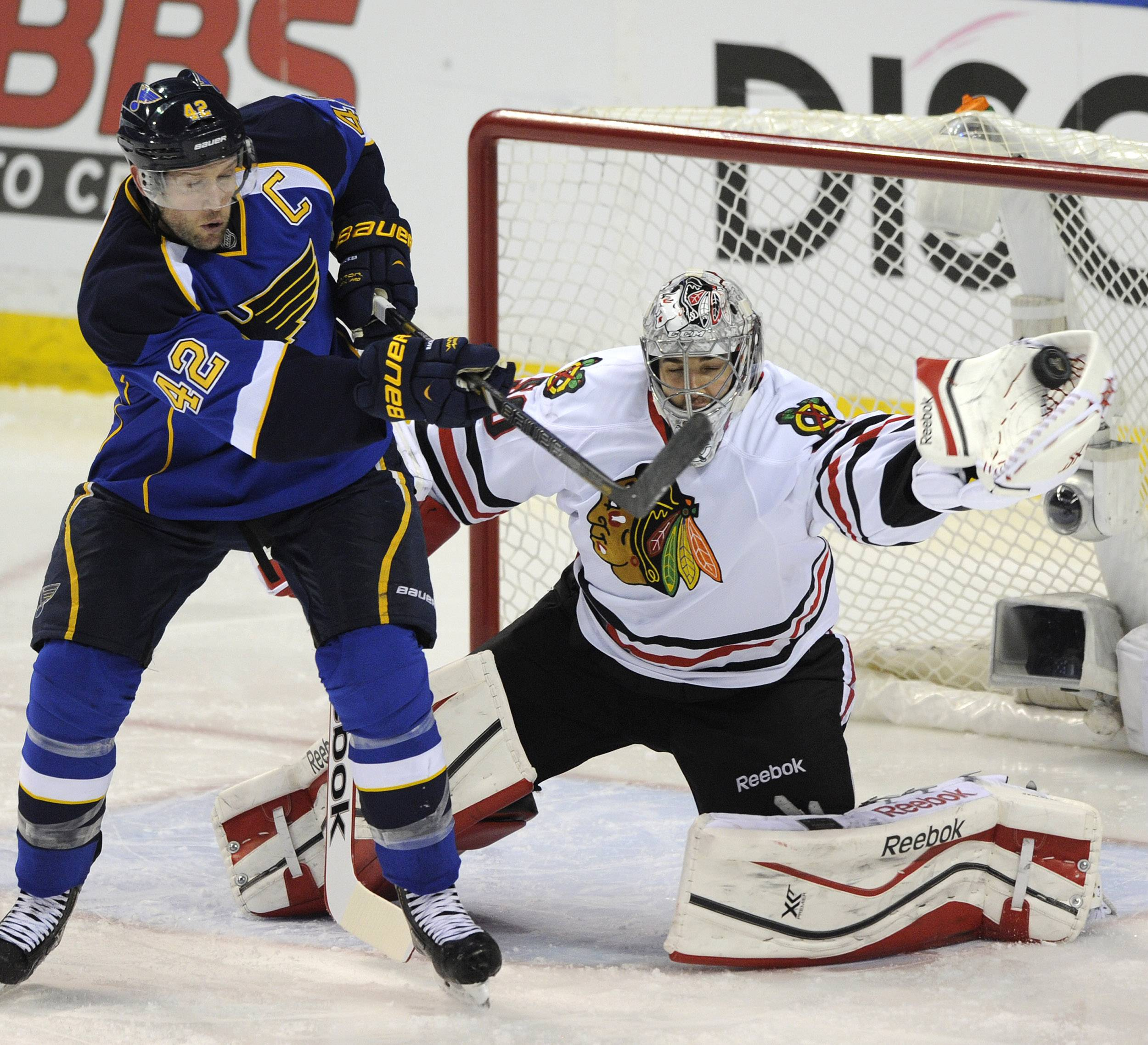 Chicago Blackhawks' goalie Corey Crawford, right, makes a glove-save against St. Louis Blues' David Backes (42) during the second period in Game 2 of a first-round NHL hockey playoff series on Saturday, April 19, 2014, in St. Louis.