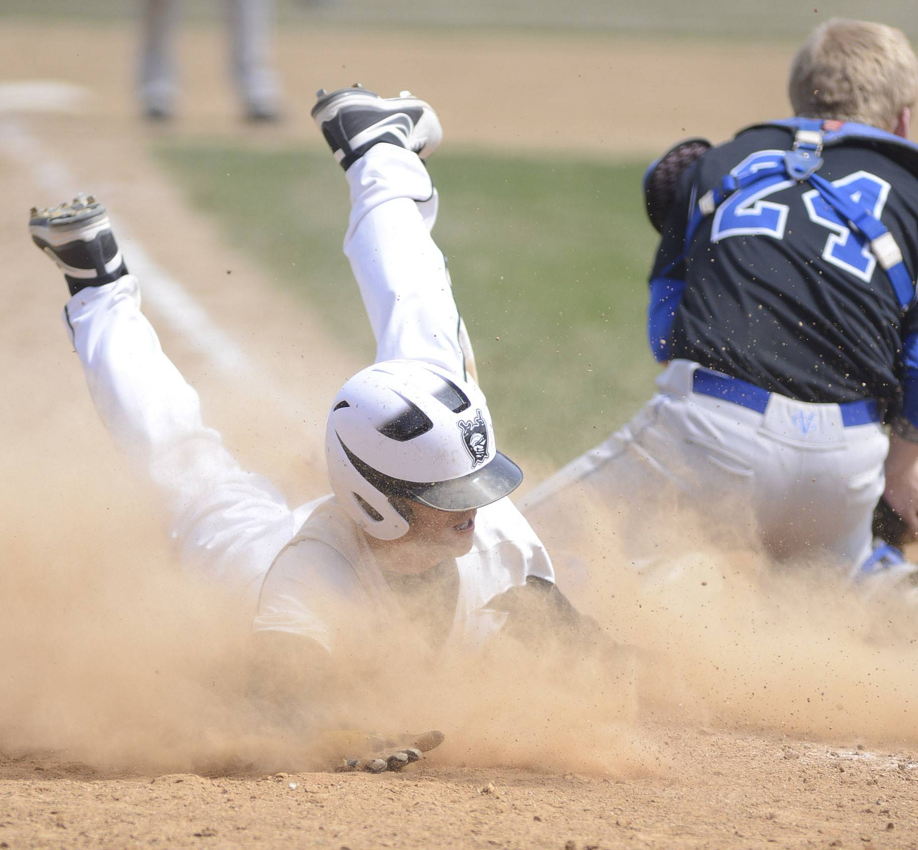 Kaneland's Joe Panico slides into home plate past Geneva catcher Nathan Montgomery to break the 6-6 tie in the ninth inning on Saturday, April 19.