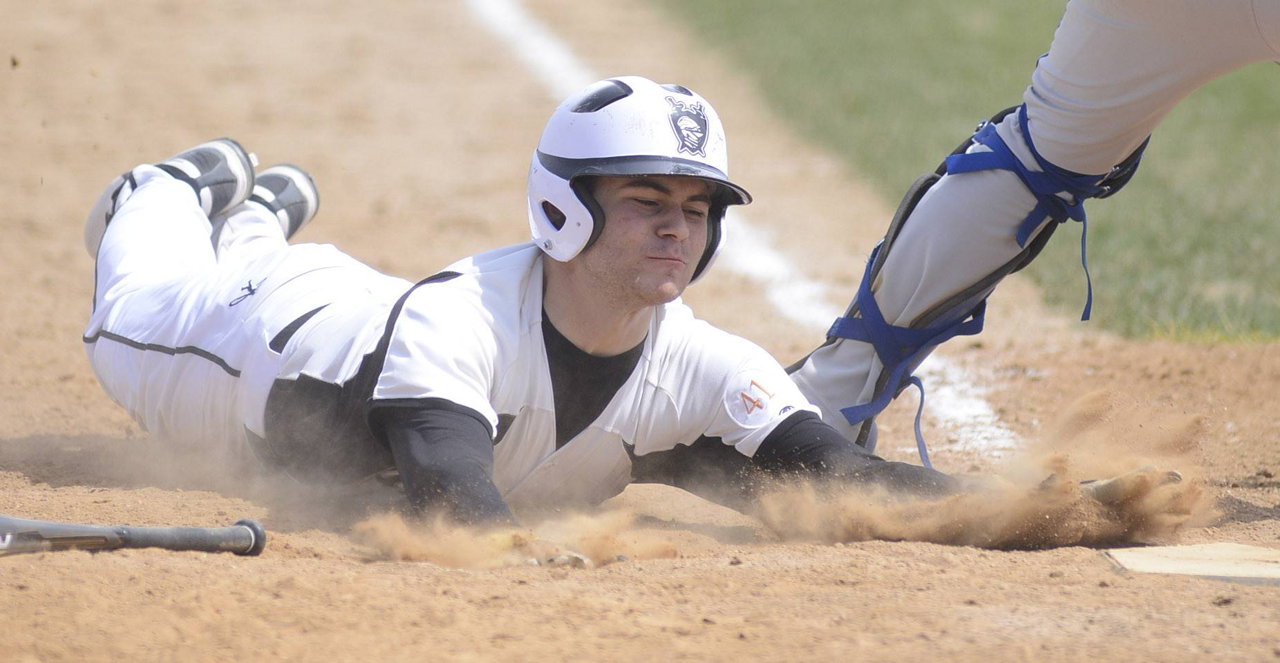 Kaneland's Joe Panico slides into home plate to break the 6-6 tie vs. Geneva in the ninth inning on Saturday, April 19.