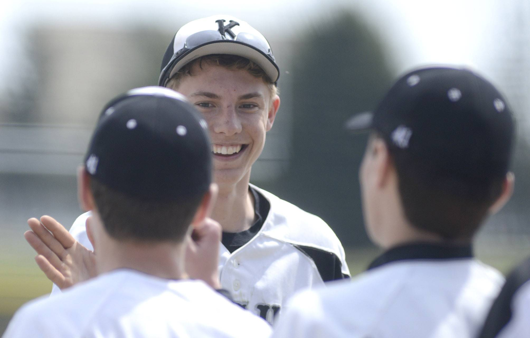 Kaneland's Nick Stratman is congratulated by teammates as he returns to the dugout after catching the final out in the top of the ninth inning.