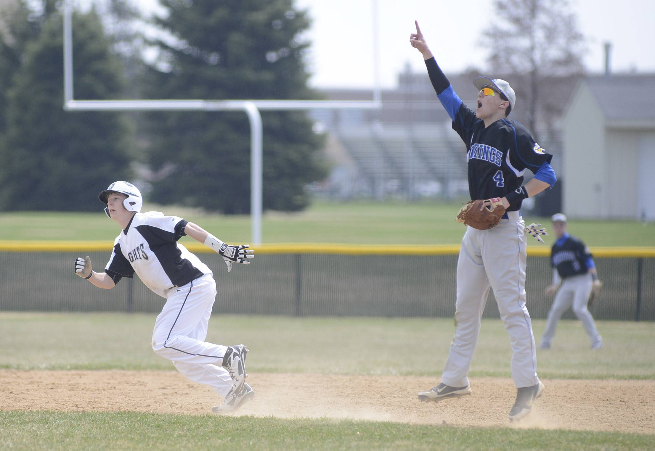 Kaneland's Jacob Bachio heads for second base while Geneva's Nick Porretto calls out the direction of a fly ball in the eighth inning on Saturday, April 19.