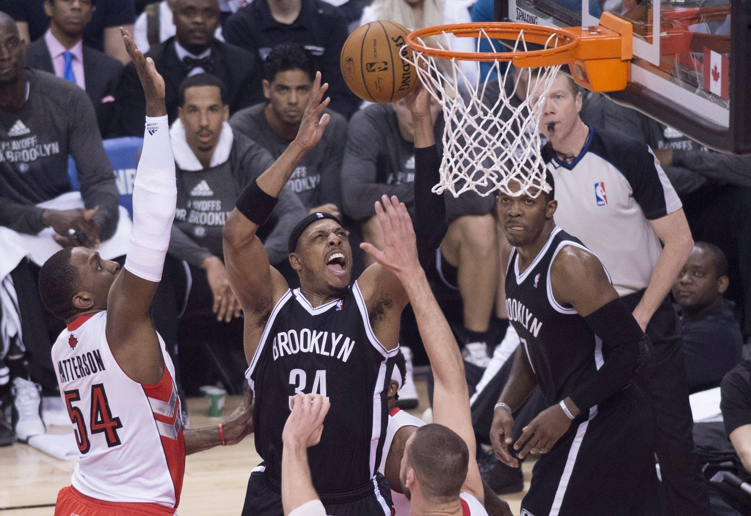 The Brooklyn Nets' Paul Pierce, center, drives to the net against Toronto Raptors Patrick Patterson, left, during Saturday's Game 1 of an opening-round NBA basketball playoff series, in Toronto.