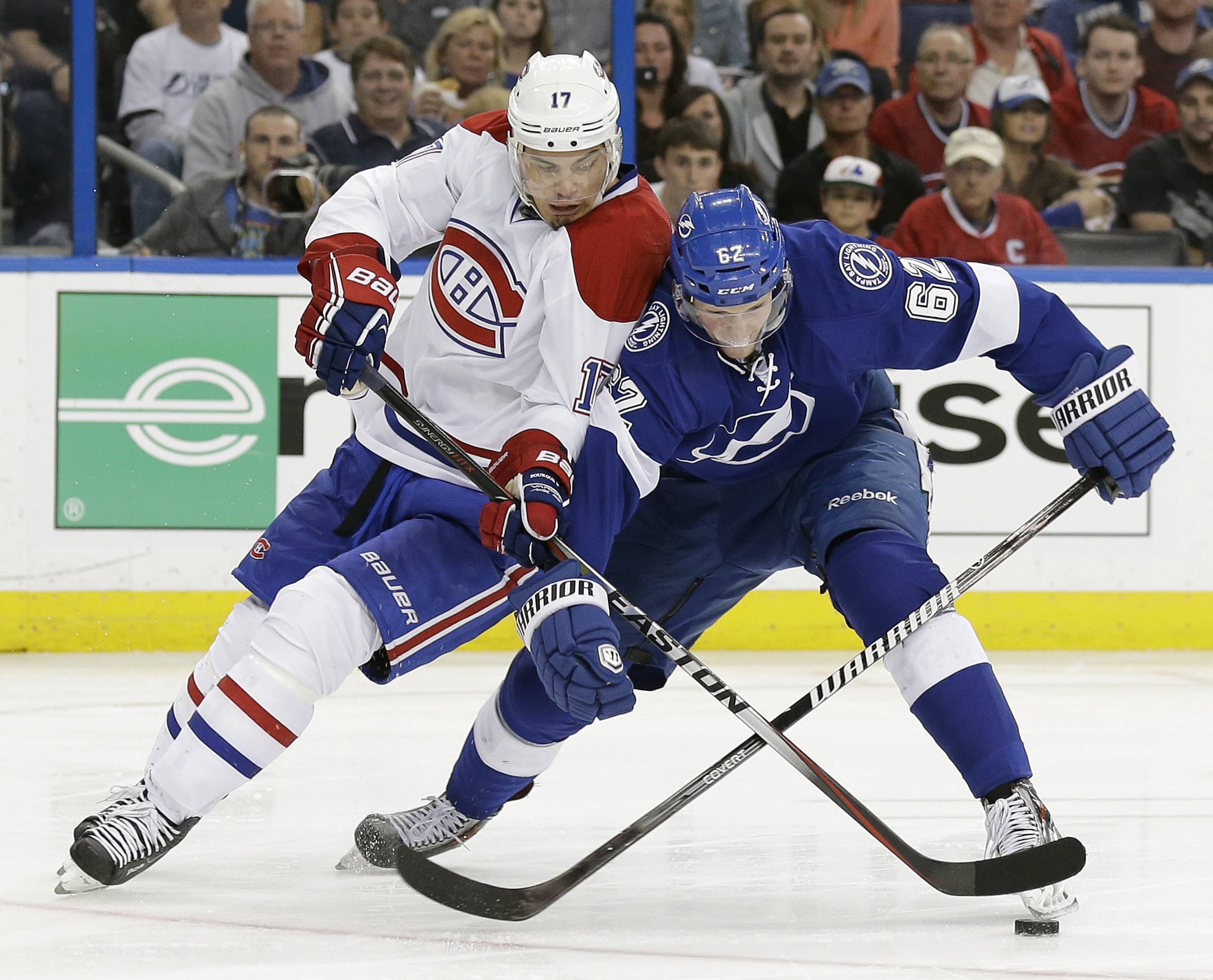 Montreal Canadiens left wing Rene Bourque (17) battles Tampa Bay Lightning defenseman Andrej Sustr (62), of the Czech Republic, for the puck during the third period of Game 2 of a first-round NHL hockey playoff series on Friday, April 18, 2014, in Tampa, Fla.