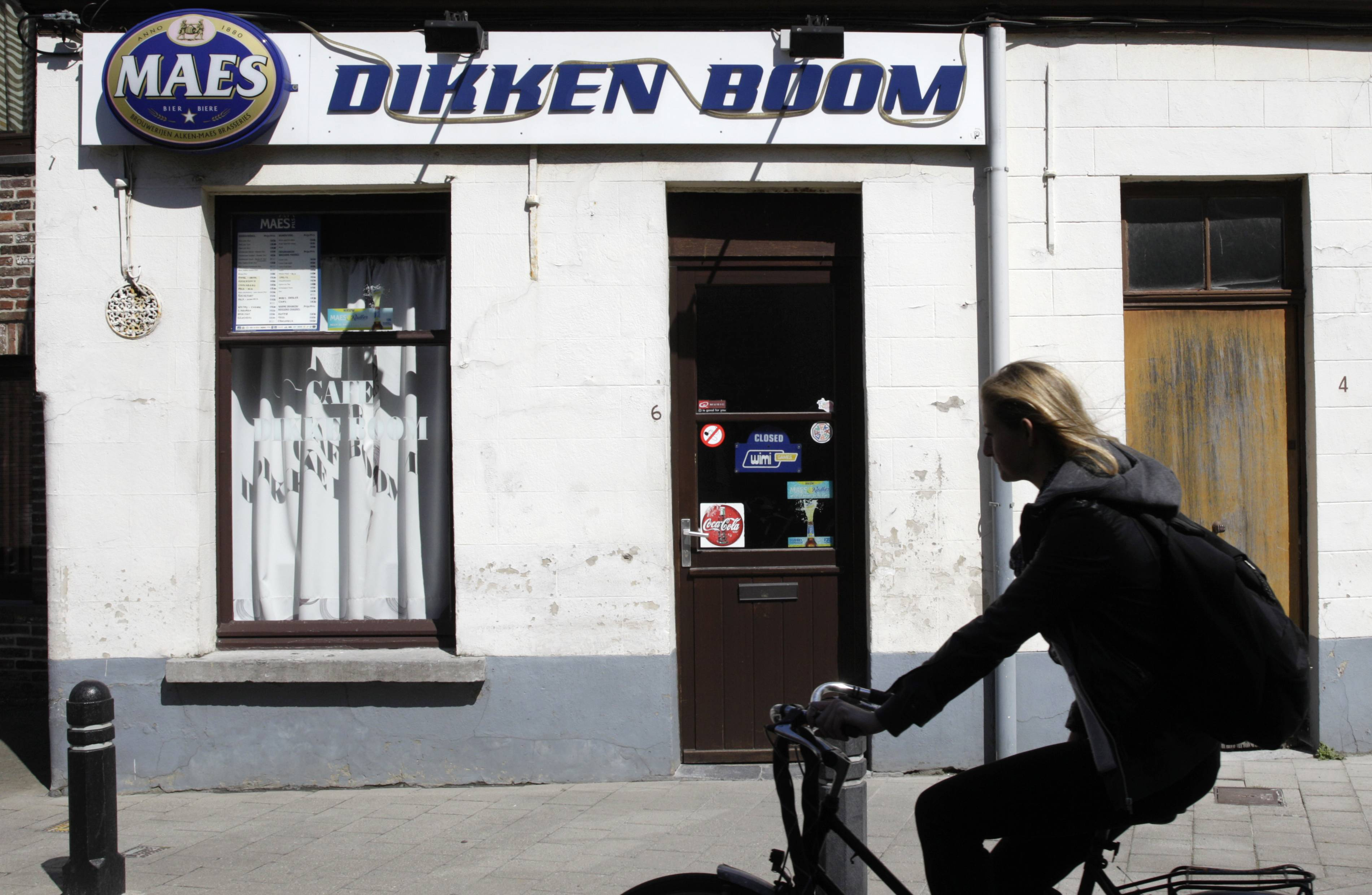 In this picture taken on Thursday, April 17, 2014, a woman cycles past a local pub in Ghent, western Belgium. Thousands of such bars in towns and villages have closed over the past decades, and on top of it, Belgians have stopped drinking like they used to. The Belgian beer federation is now trying to rekindle local faith in the drink with a 'Proud of Belgian Beers' campaign.
