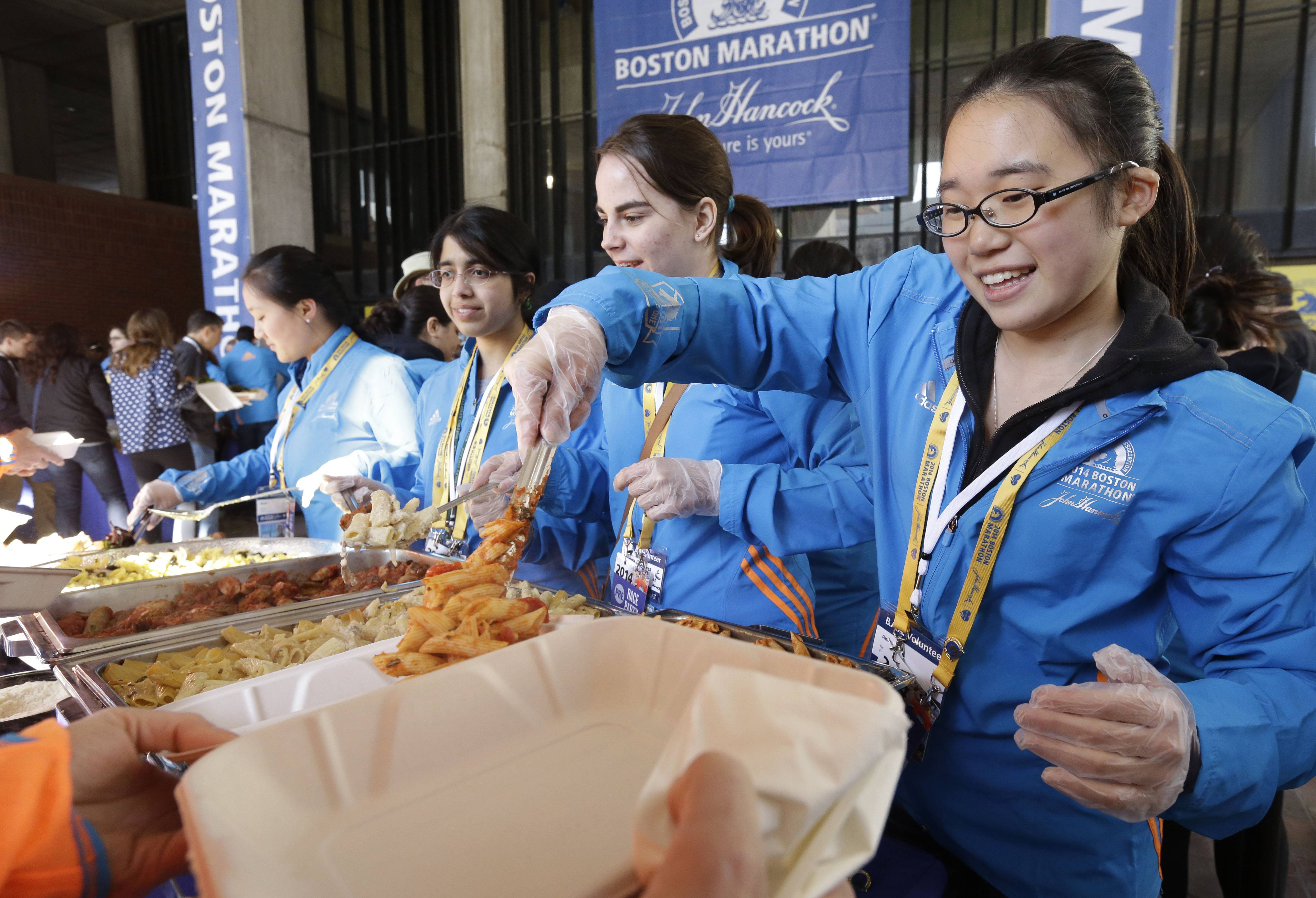 Wellesley College student Akiho Saito, of Tokyo, right, serves pasta during a Boston Marathon pre-race dinner at Boston City Hall Sunday. With an expanded field of runners and the memory of last year's bombings the 2014 Boston Marathon could bring an unprecedented wave of visitors to the area.