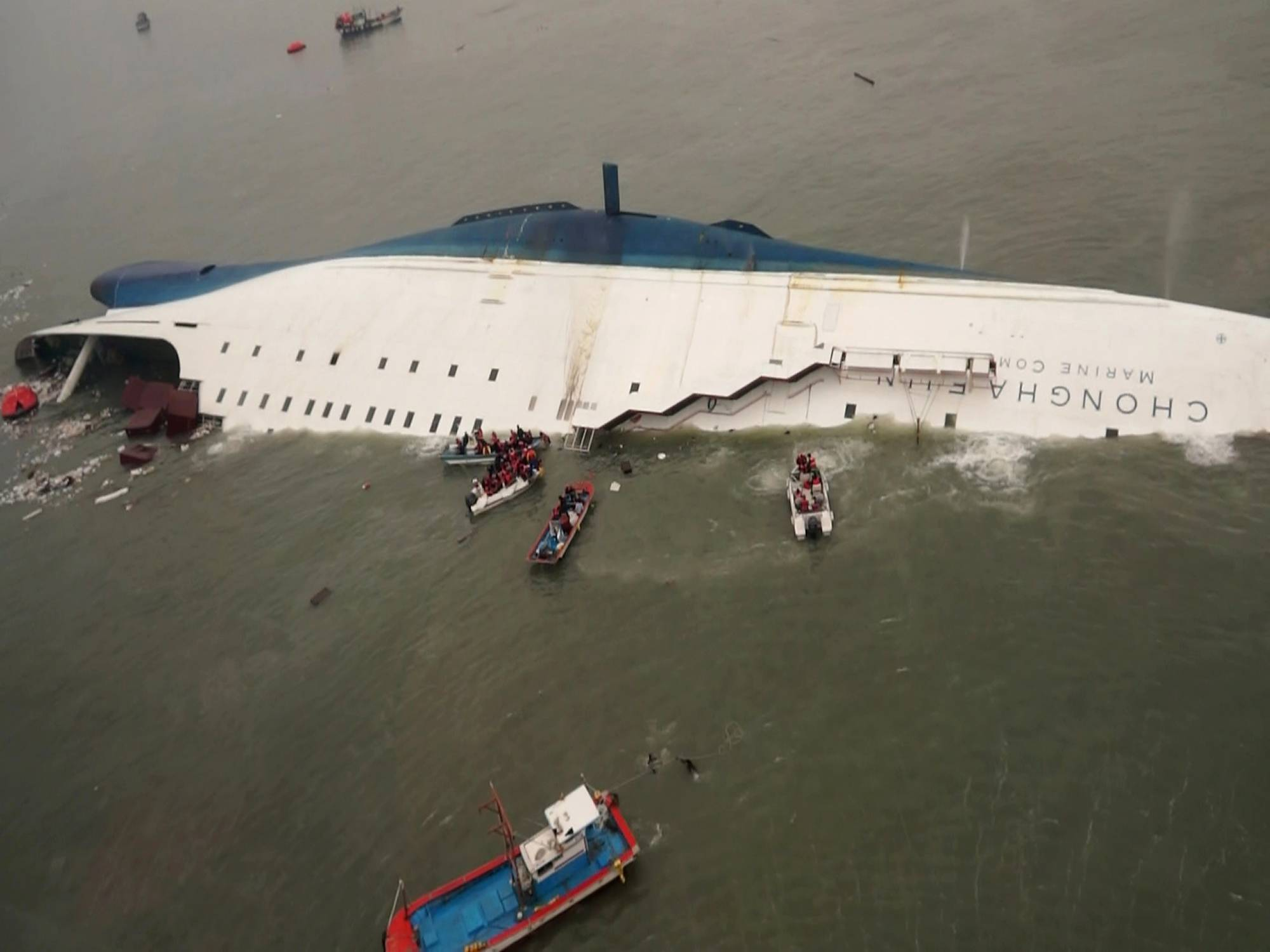 South Korean rescue team boats and fishing boats are seen last week trying to rescue passengers of the sinking Sewol ferry. Maritime experts are asking why passengers were told to stay in their rooms rather than climb on deck.