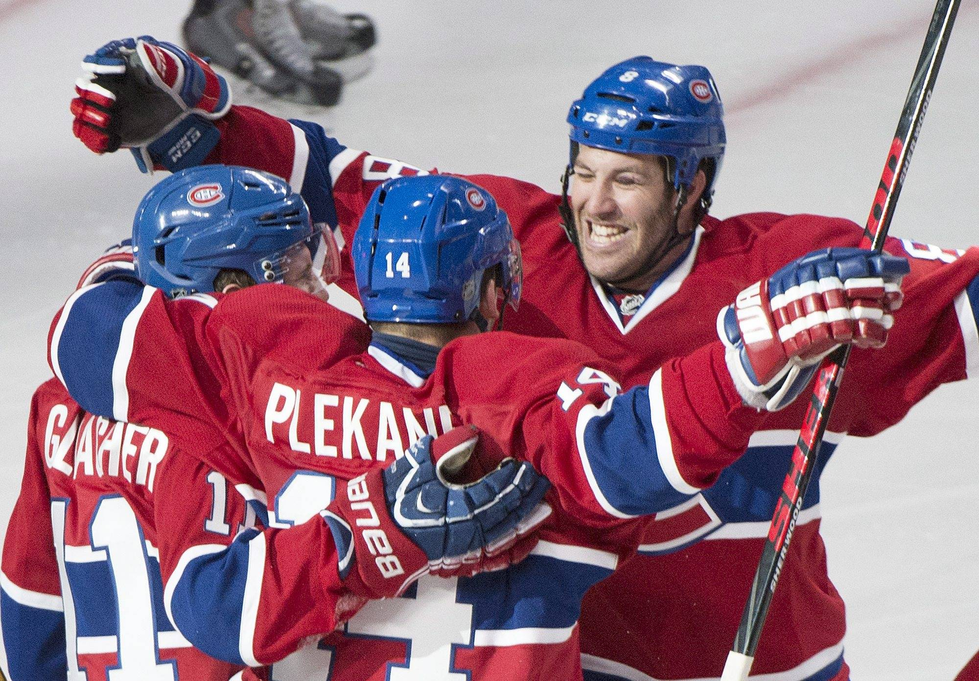 Montreal Canadiens' Tomas Plekanec, centre, celebrates with teammates Brandon Prust, right, and Brendan Gallagher after scoring against the Tampa Bay Lightning during third period NHL Stanley Cup hockey playoff action in Montreal, Sunday, April 20, 2014.