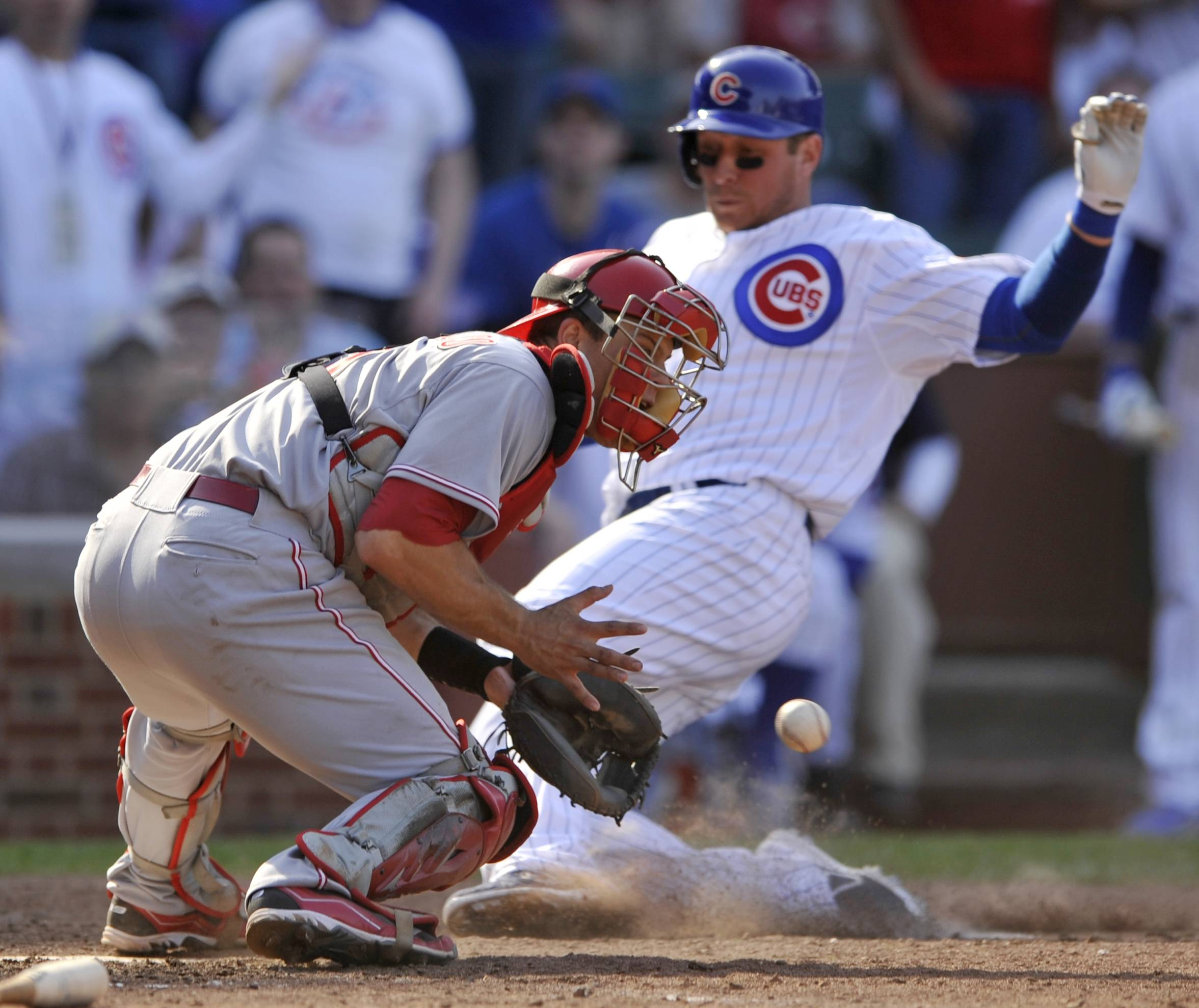 Cincinnati Reds catcher Devin Mesoraco front, catches the throw while Chicago Cubs' Ryan Sweeney slides safely into home plate on a single hit by Nate Schierholtz during the seventh inning of a baseball game in Chicago, Sunday, April 20, 2014.