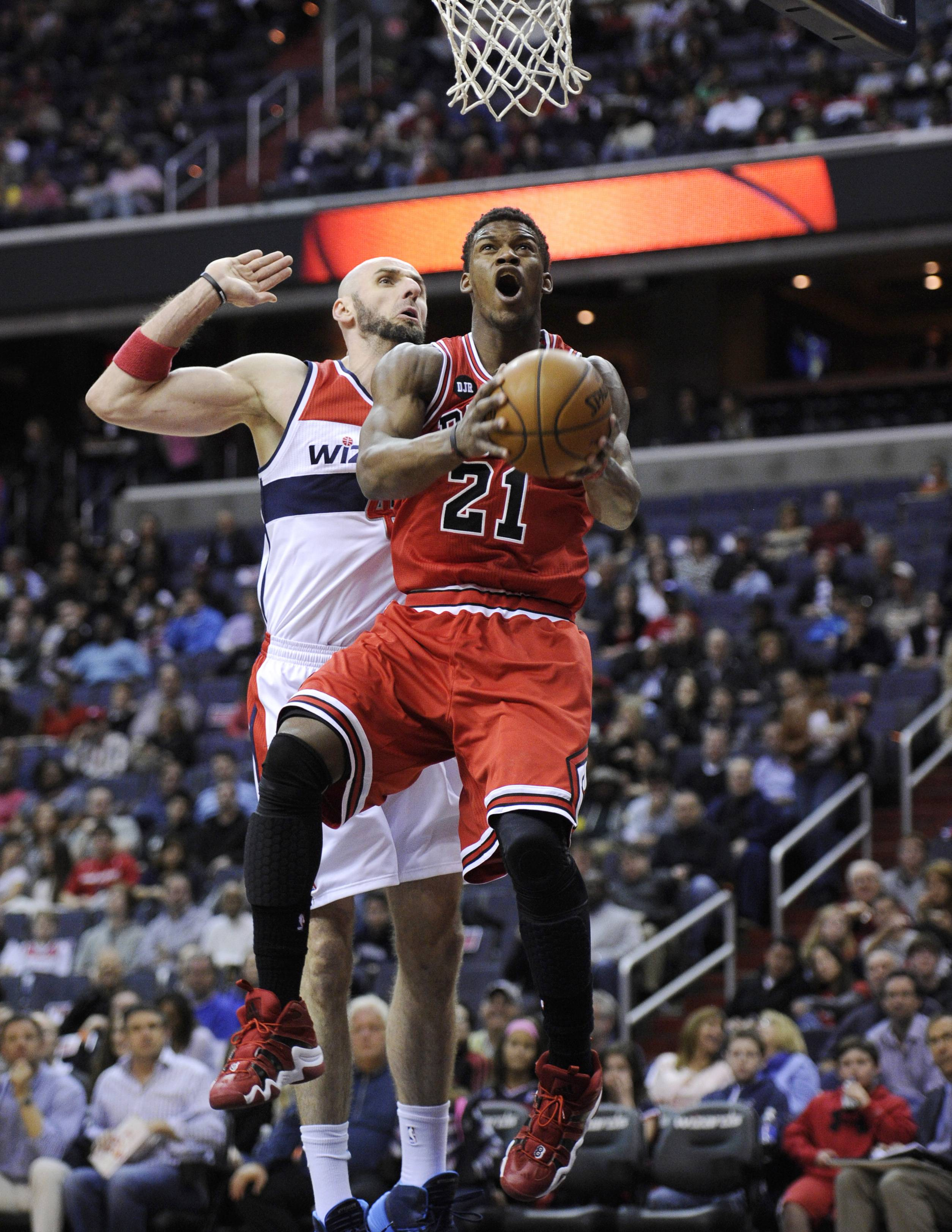 Bulls guard Jimmy Butler (21) goes to the basket against Washington Wizards center Marcin Gortat, back, of Poland, during the first half of an NBA basketball game, Saturday, April 5, 2014, in Washington.